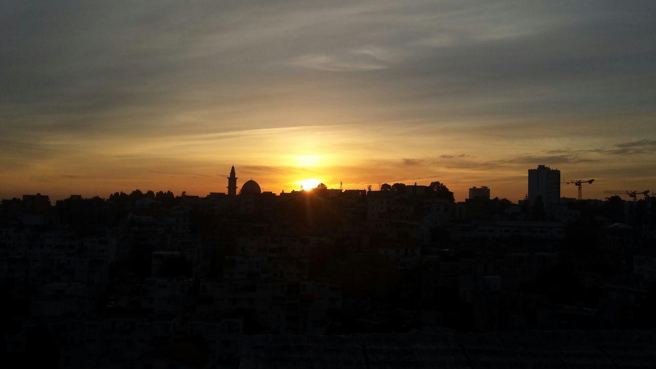 sunset, architecture, cityscape, building exterior, built structure, city, silhouette, no people, sky, sun, travel destinations, outdoors, skyscraper