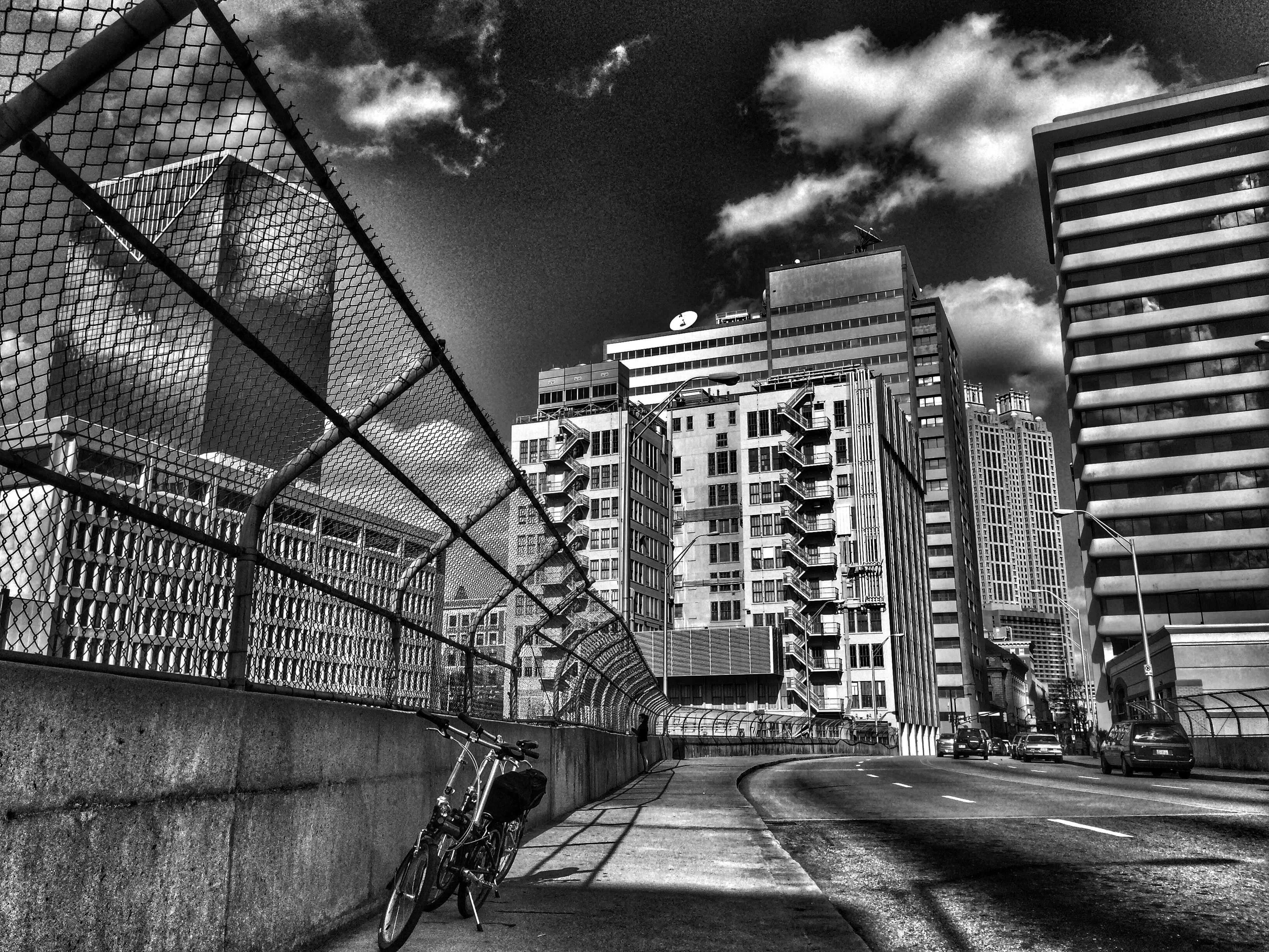 architecture, built structure, building exterior, sky, cloud - sky, the way forward, low angle view, city, railing, cloud, cloudy, street, building, transportation, day, outdoors, diminishing perspective, road, modern, no people