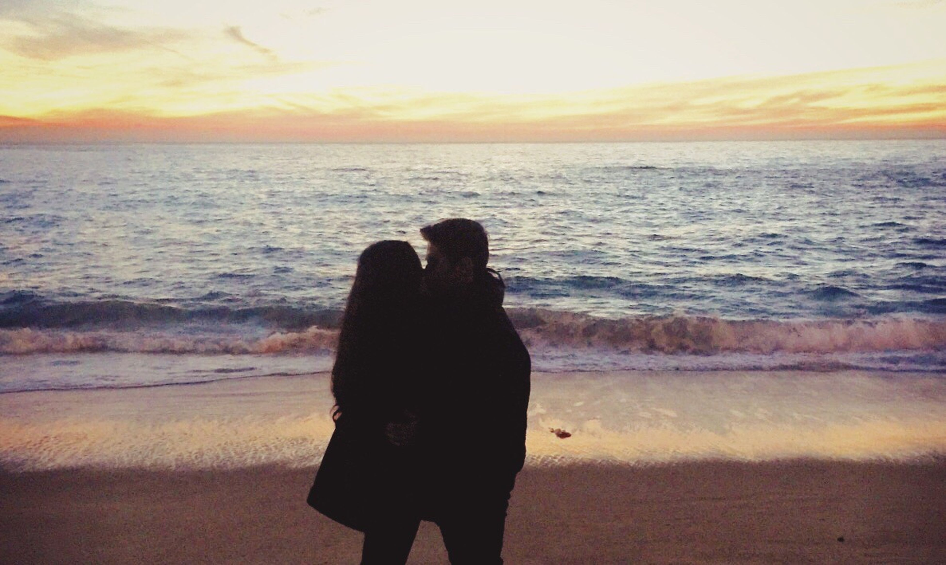 sea, two people, togetherness, sunset, real people, love, horizon over water, leisure activity, beach, nature, scenics, water, standing, sky, bonding, beauty in nature, lifestyles, embracing, outdoors, women, men, friendship, wave, day, people