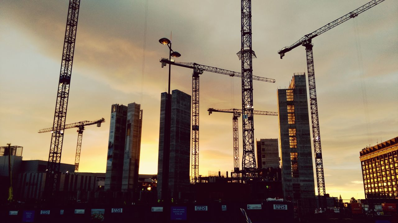 architecture, development, construction site, built structure, building exterior, city, construction, sky, crane - construction machinery, crane, outdoors, skyscraper, progress, no people, sunset, tall, low angle view, cityscape, day