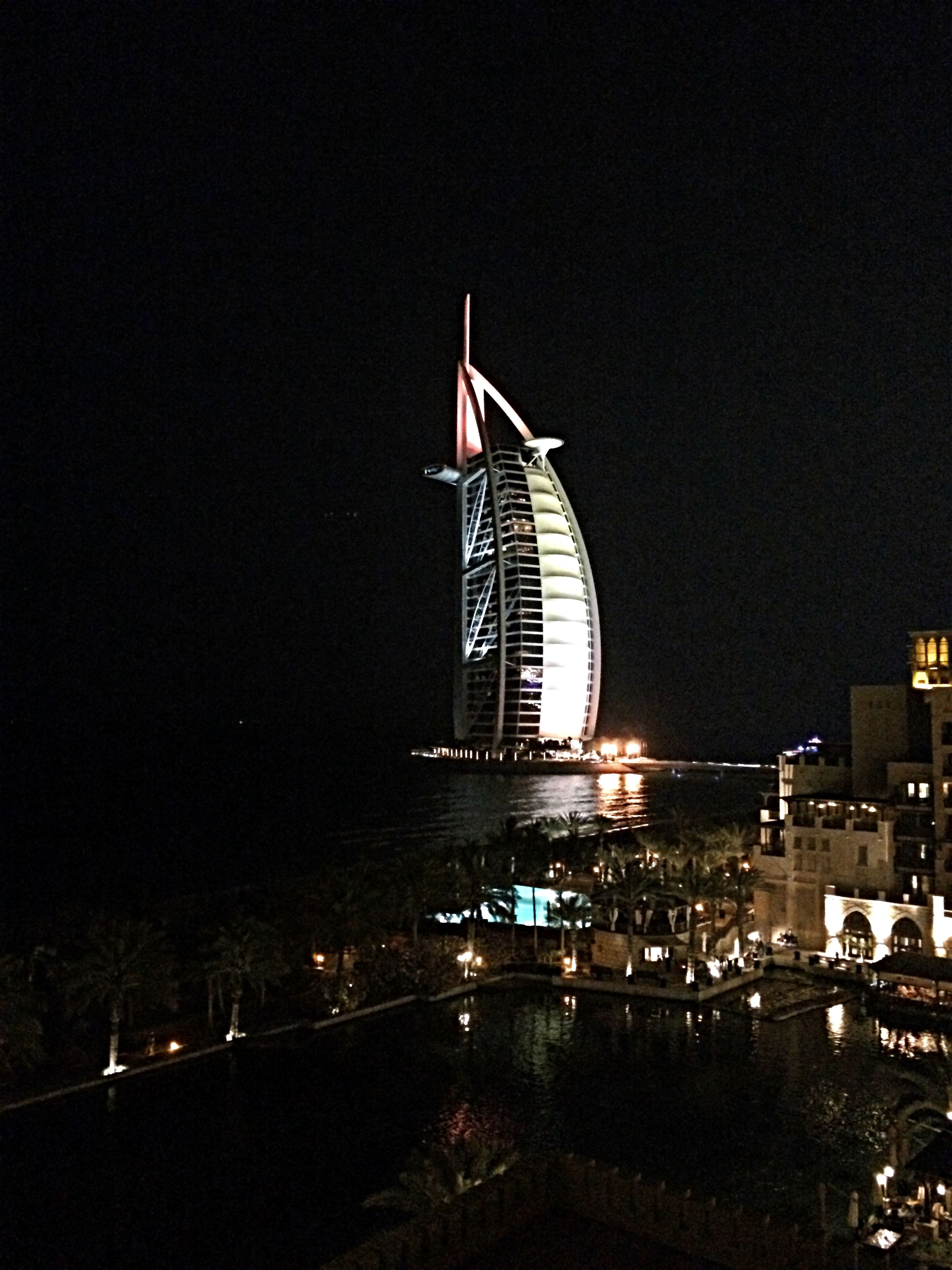 architecture, building exterior, built structure, city, night, nautical vessel, transportation, clear sky, modern, water, illuminated, river, skyscraper, copy space, boat, mode of transport, office building, cityscape, travel, outdoors