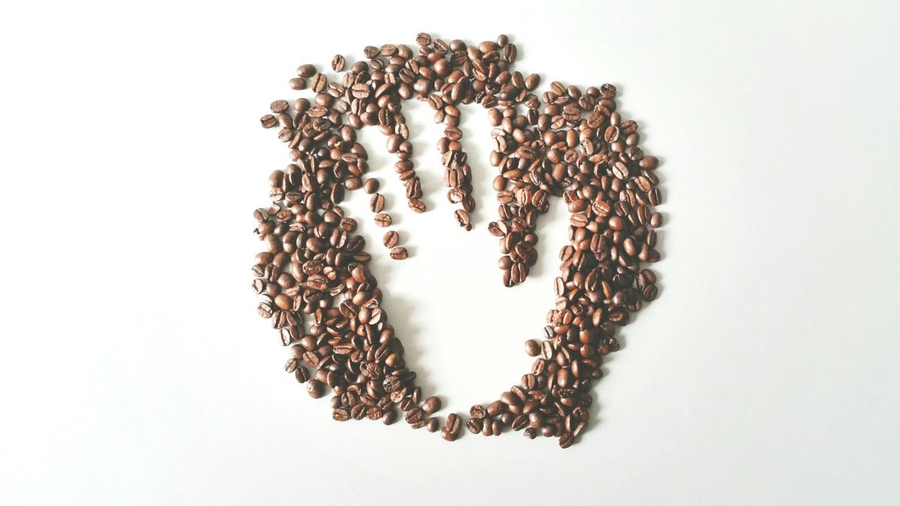 High Angle View Of Hand Made In Coffee Bean Heap On White Background