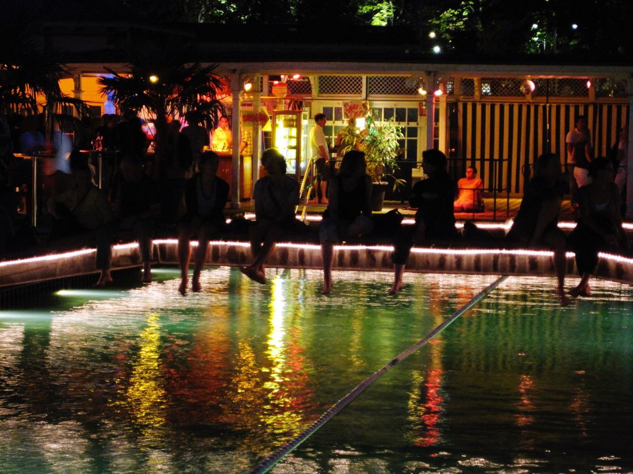 water, swimming pool, night, illuminated, large group of people, leisure activity, outdoors, real people, vacations, men, people