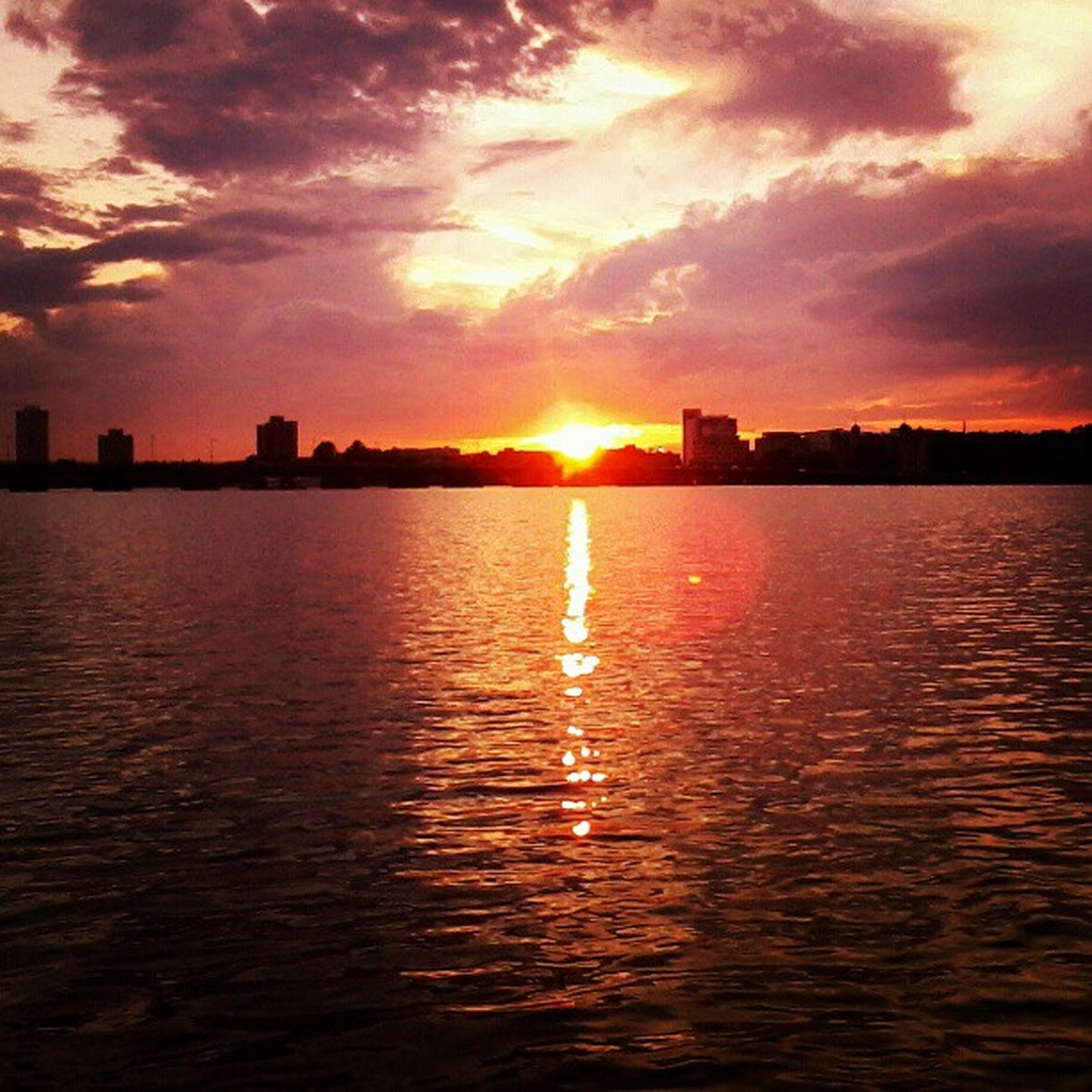 sunset, sun, water, sky, waterfront, reflection, silhouette, building exterior, scenics, orange color, sea, cloud - sky, beauty in nature, sunlight, tranquil scene, architecture, built structure, rippled, tranquility, idyllic