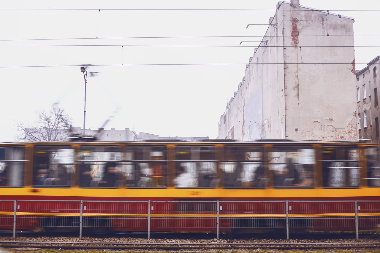 transportation, rail transportation, public transportation, mode of transport, on the move, connection, train - vehicle, railroad station, built structure, building exterior, outdoors, architecture, passenger train, railroad track, day, motion, no people, sky, city, speed, railroad station platform