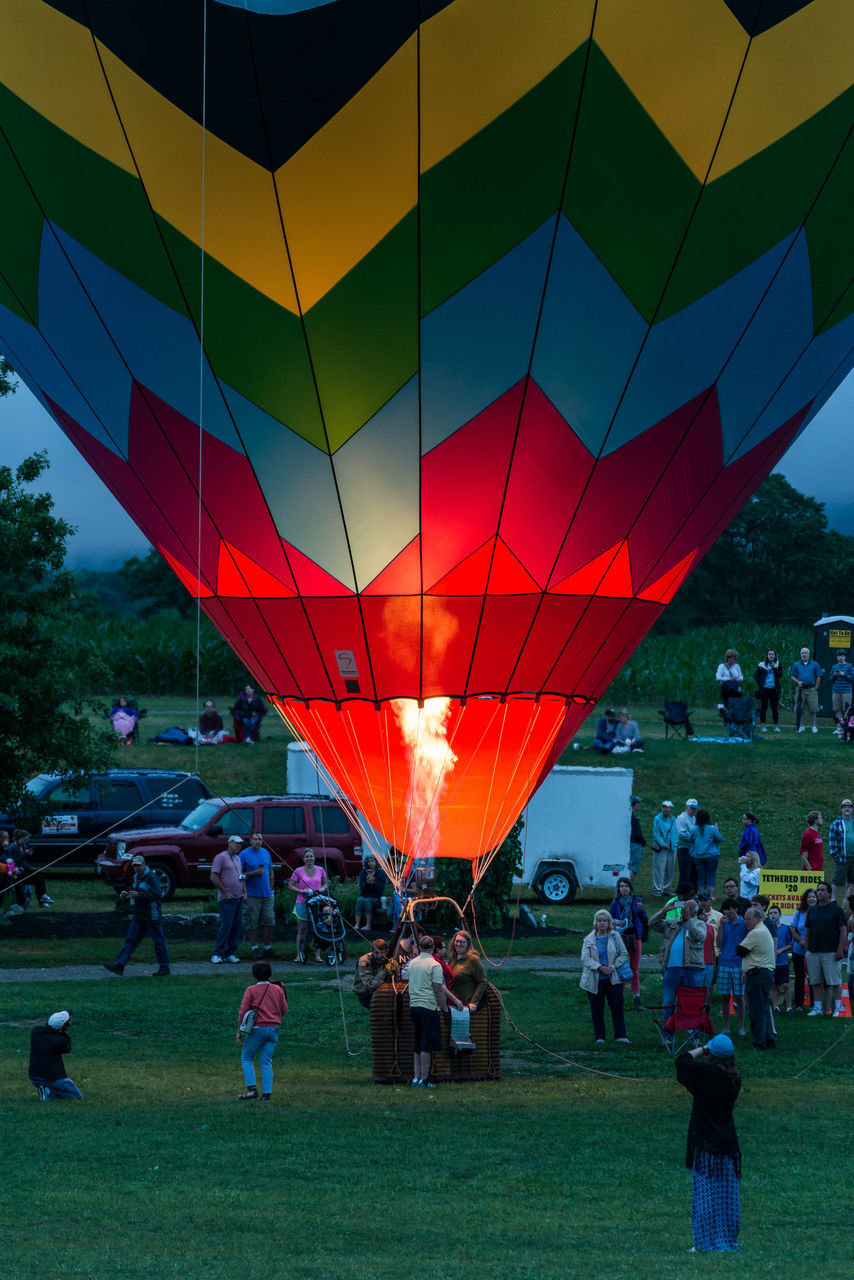 large group of people, real people, men, leisure activity, enjoyment, women, lifestyles, grass, outdoors, mixed age range, fun, crowd, togetherness, performance, standing, sky, ballooning festival, day, sport, multi colored, architecture, building exterior, hot air balloon, adult, people