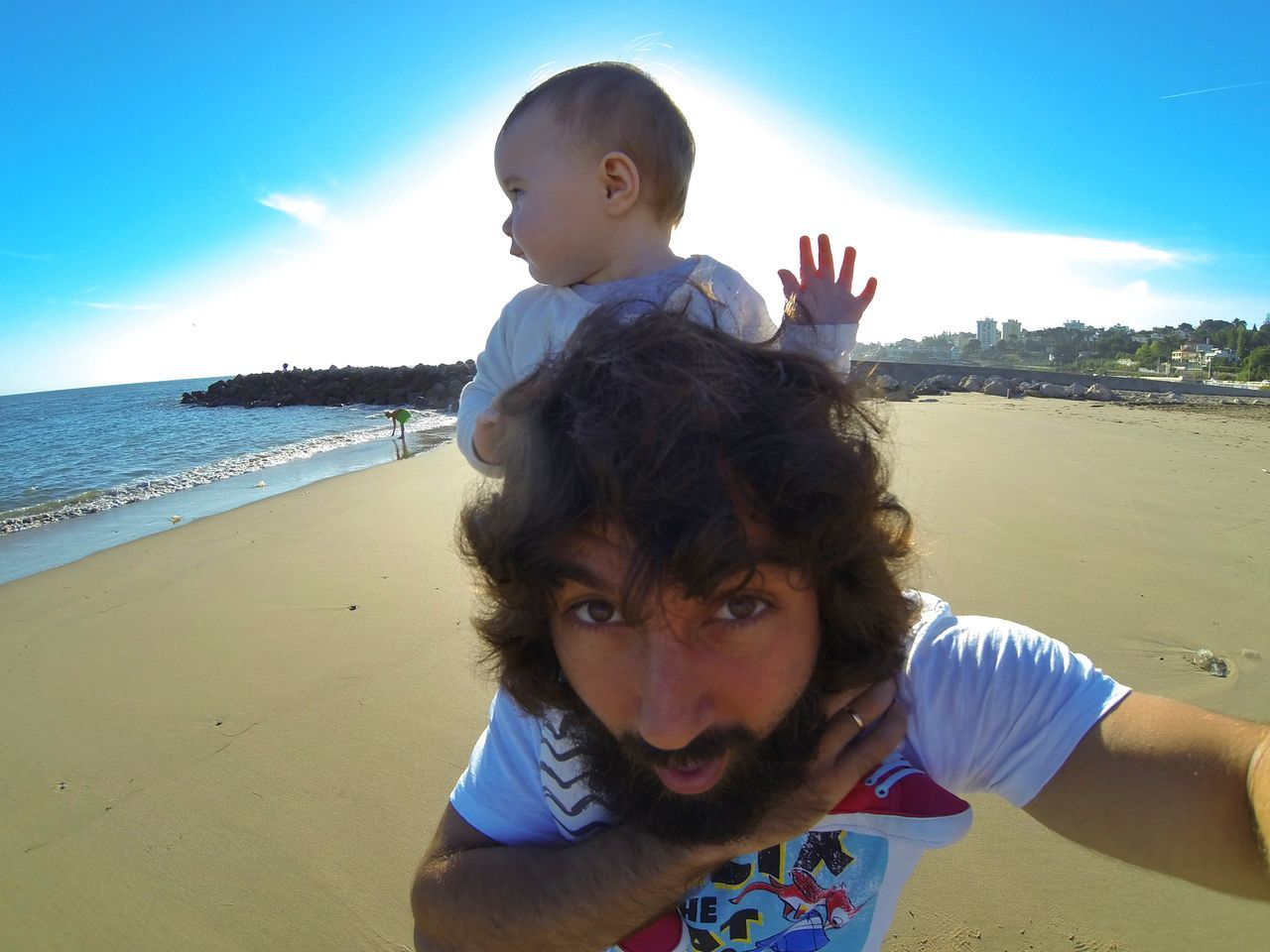 Portrait Of Father Carrying Daughter On Shoulder At Beach Against Sky