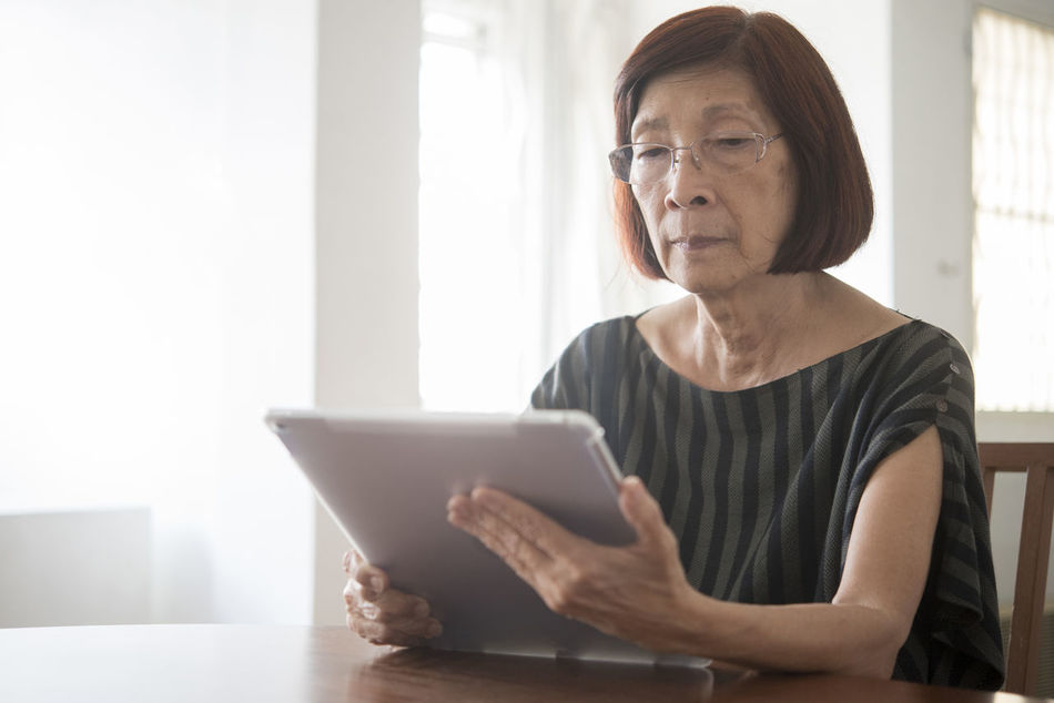 Adult Casual Clothing Communication Connection Day Digital Tablet Domestic Life Eyeglasses  Front View Holding Home Interior Indoors  Internet Lifestyles Mature Adult Mature Women One Person People Real People Sitting Technology Touch Screen Wireless Technology Women