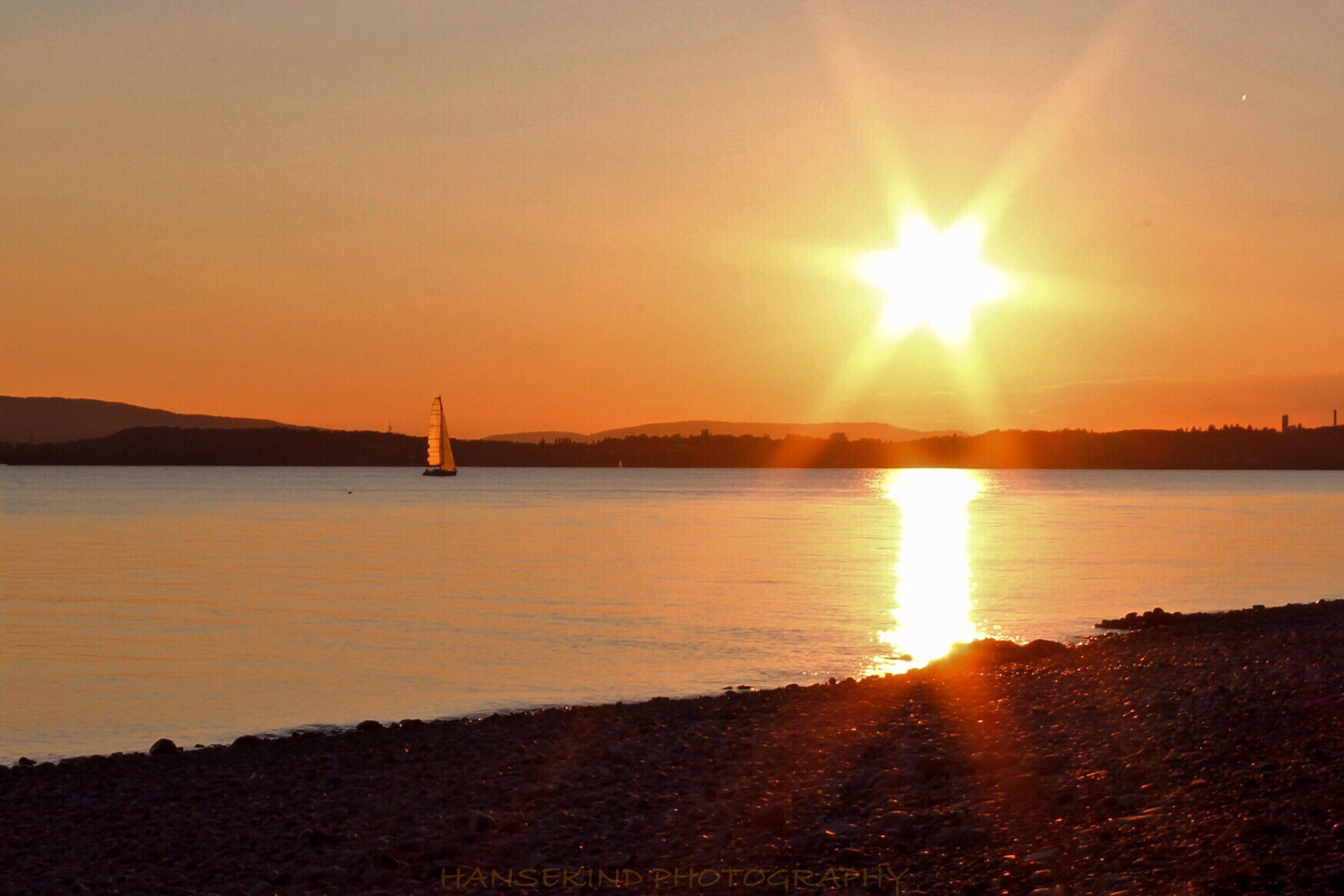 sun, sunset, water, scenics, tranquil scene, mountain, tranquility, sunlight, beauty in nature, sunbeam, orange color, lens flare, reflection, silhouette, nature, sea, idyllic, sky, beach, clear sky