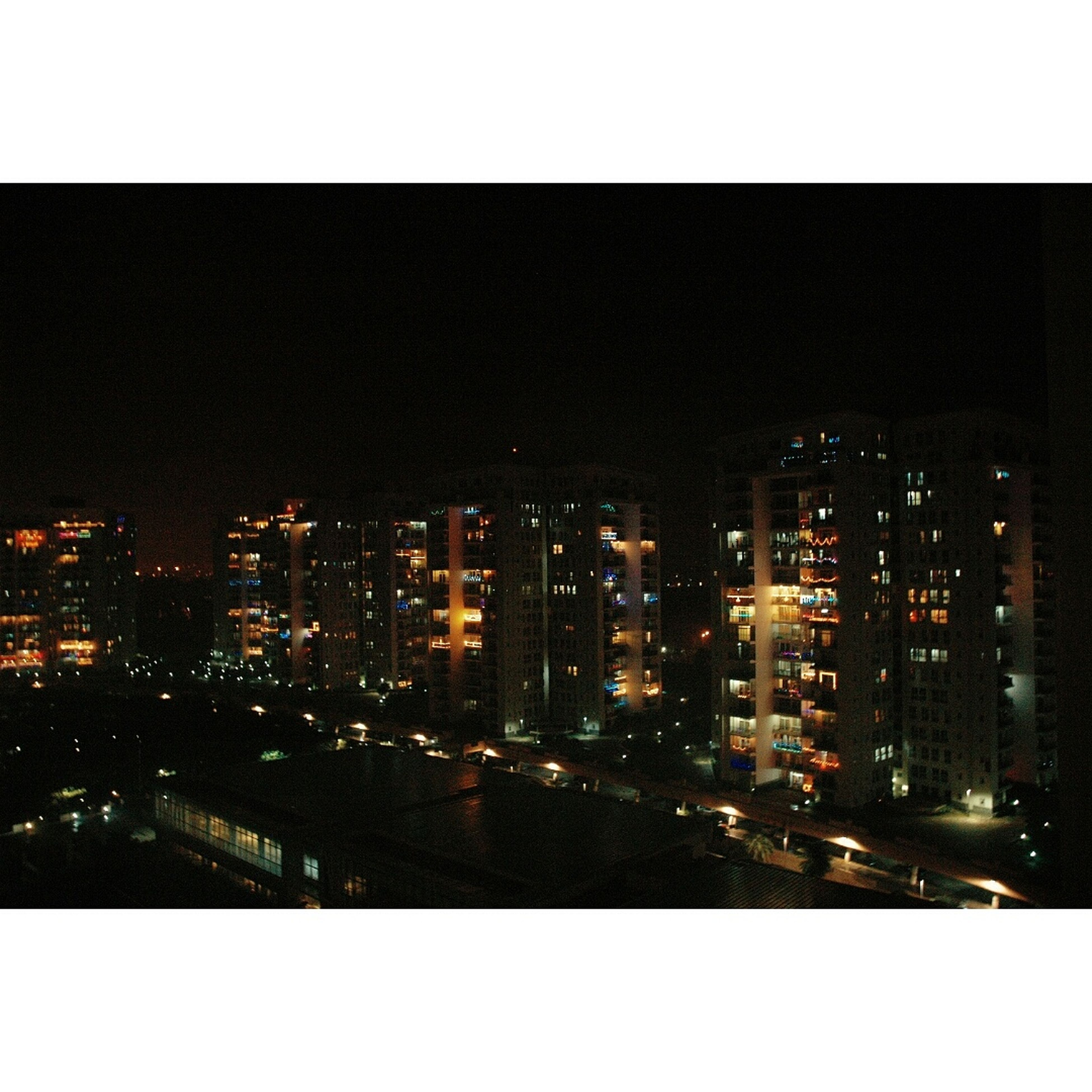 building exterior, city, transfer print, architecture, cityscape, built structure, skyscraper, illuminated, auto post production filter, night, crowded, office building, residential building, high angle view, city life, modern, urban skyline, tower, residential district, tall - high