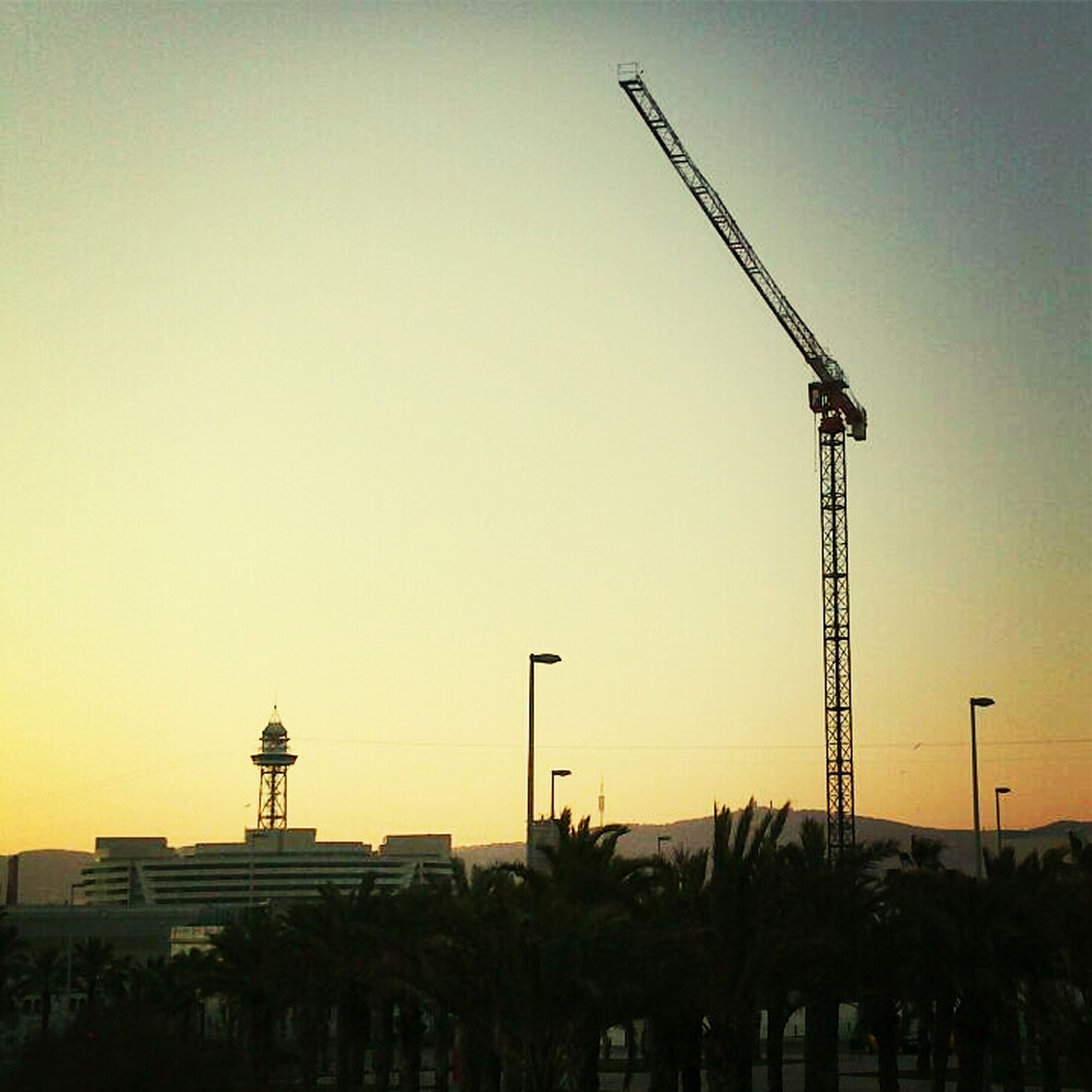 clear sky, built structure, sunset, architecture, building exterior, copy space, fuel and power generation, technology, crane - construction machinery, low angle view, development, construction site, orange color, environmental conservation, crane, wind power, silhouette, industry, alternative energy, renewable energy