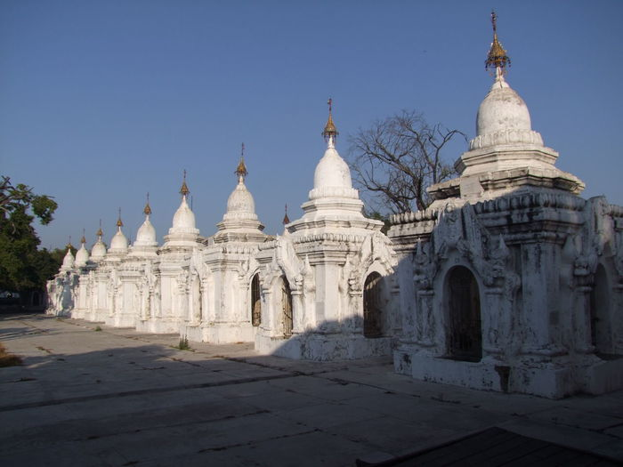 A few of the 729 whitewashed pagodas housing the world's largest book (erected in 1872 for theFifth Buddhist Synod) Bible Blue Sky Buddhism Buddhism Culture Buddhist Pagodas Buddhist Temple Composition Distant Perspective Full Frame Kuthodaw Pagoda Line Of Pagodas Mandalay Myanmar No People Outdoor Photography Place Of Prayer Place Of Worship Sunlight And Shadow Tourism Tourist Attraction  Tourist Destination Trees Unusual White Washed Building Worlds Largest Book