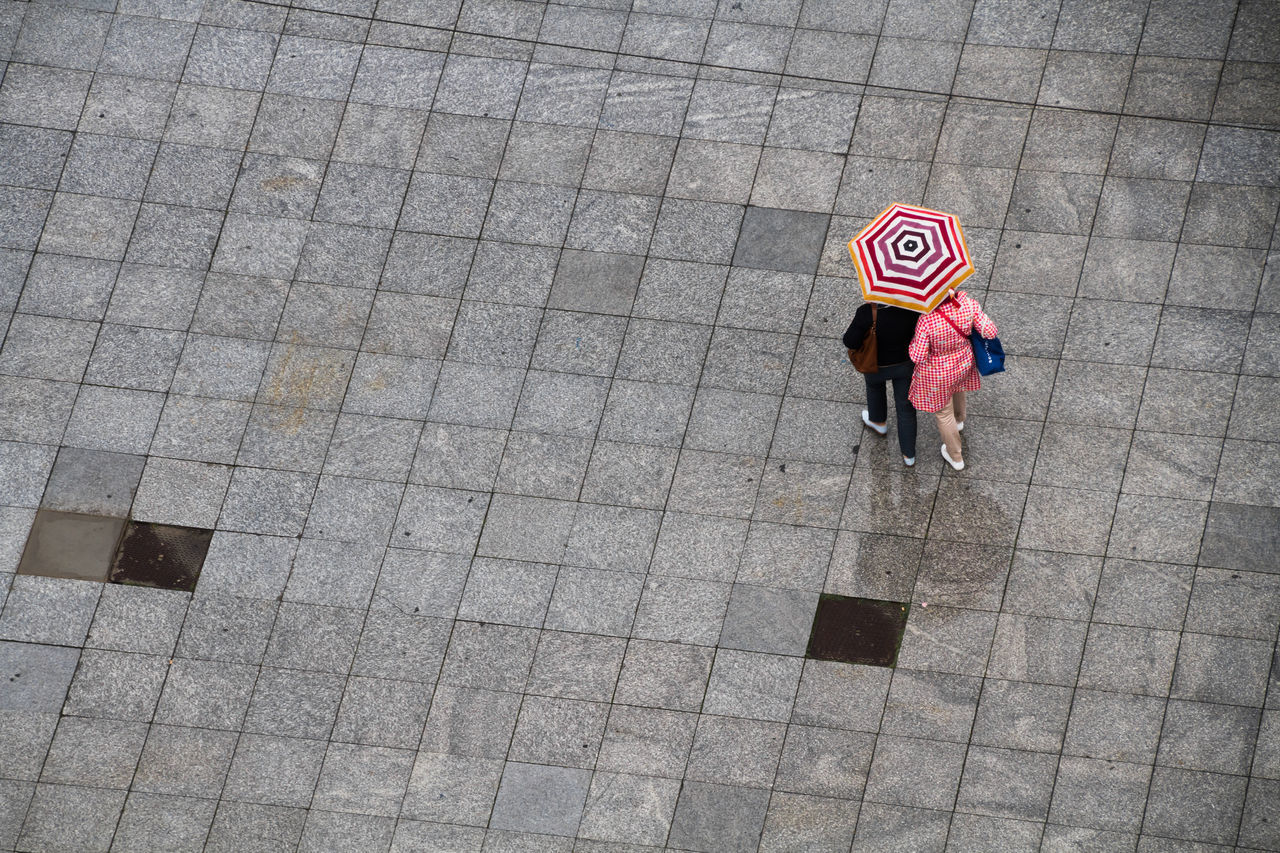 Walking in the rain Copy Space Day Full Length High Angle View Lifestyles Looking Down Outdoors People Rain Real People Rear View Suitable For Adding Text Two People Unbrella Walking Weather