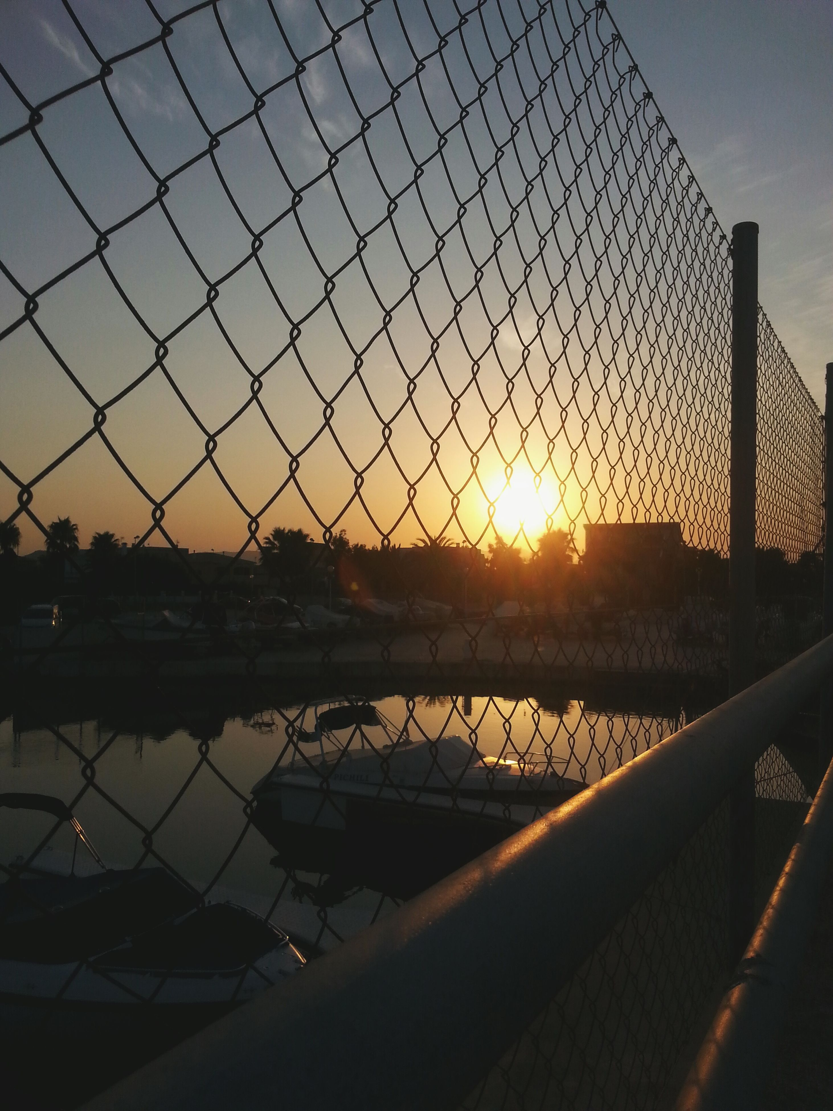sunset, sun, orange color, silhouette, sky, water, scenics, tranquility, sunlight, tranquil scene, reflection, beauty in nature, fence, nature, idyllic, chainlink fence, sea, lake, no people, sunbeam