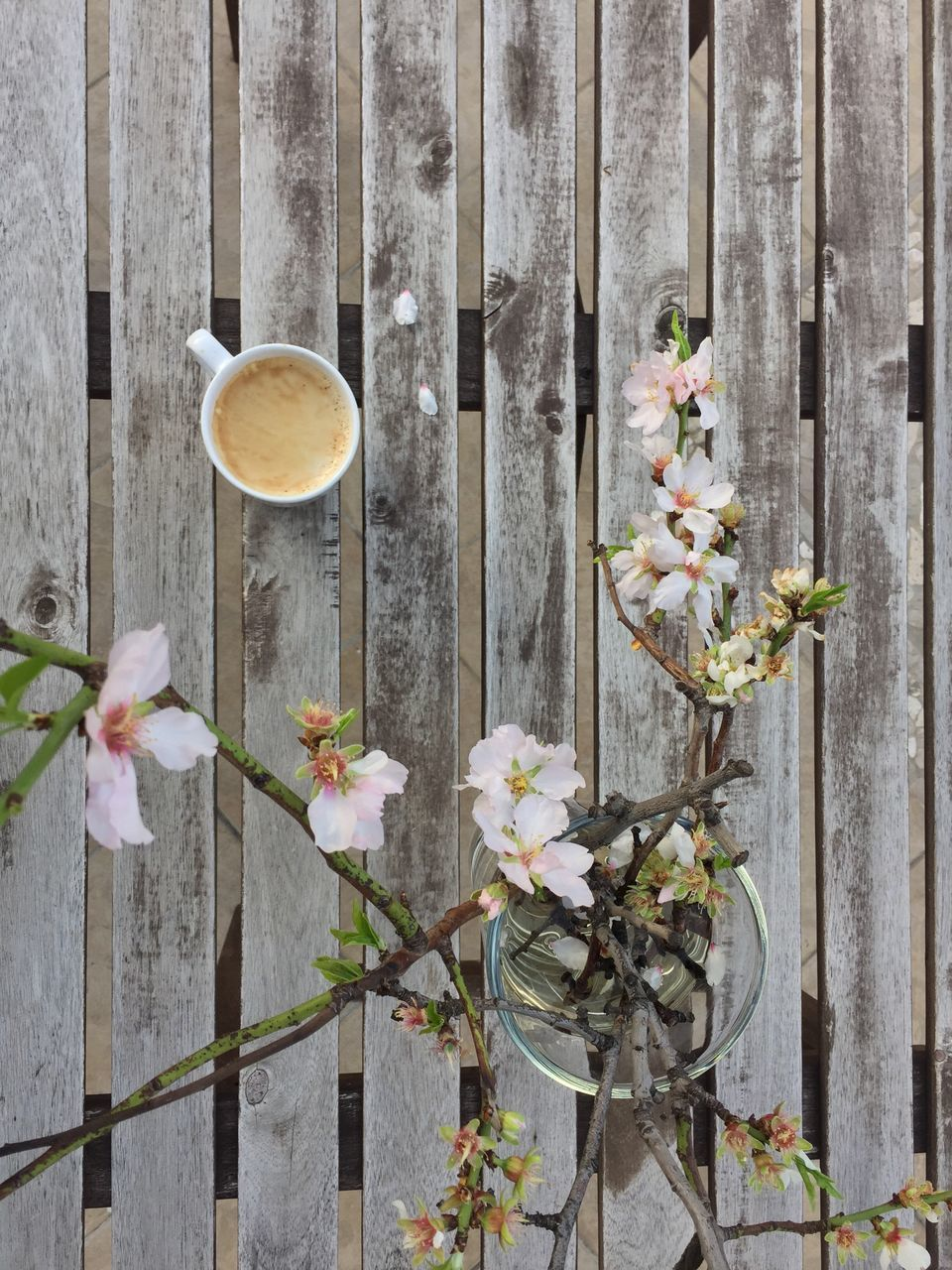 High Angle View Of Coffee Cup By Flower Vase On Wooden Table