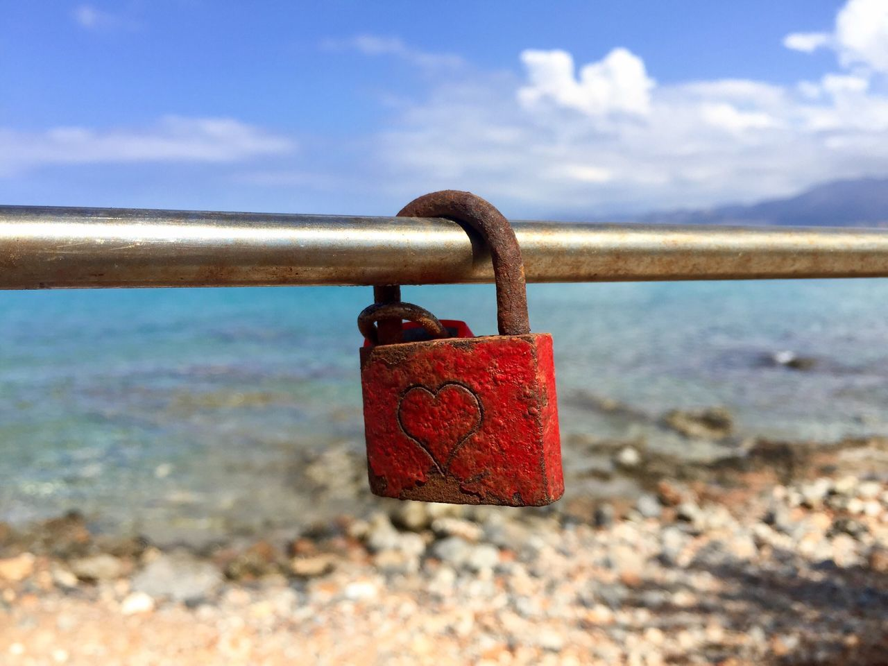 Red padlock with heart on it on a bridge over the sea Padlock Metal Safety Love Lock Security Close-up Protection Lock Sky Love Focus On Foreground Outdoors Day No People Hope Cloud - Sky Water Bridge Sea Lock Love Padlock Summer