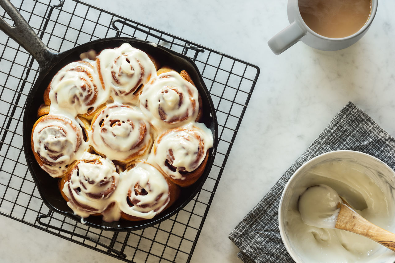 Iced cinnamon buns in a cast iron skillet Baked Baked Goods Baking Cast Iron Cast Iron Skillet Cinnamon Buns Cinnamon Roll  Cinnamon Rolls Coffee Cream Cheese Frosting Dessert Drink Food Food And Drink Gray Grey Horizontal Iced Icing Marble Mug Skillet Sweets Tea Visual Feast