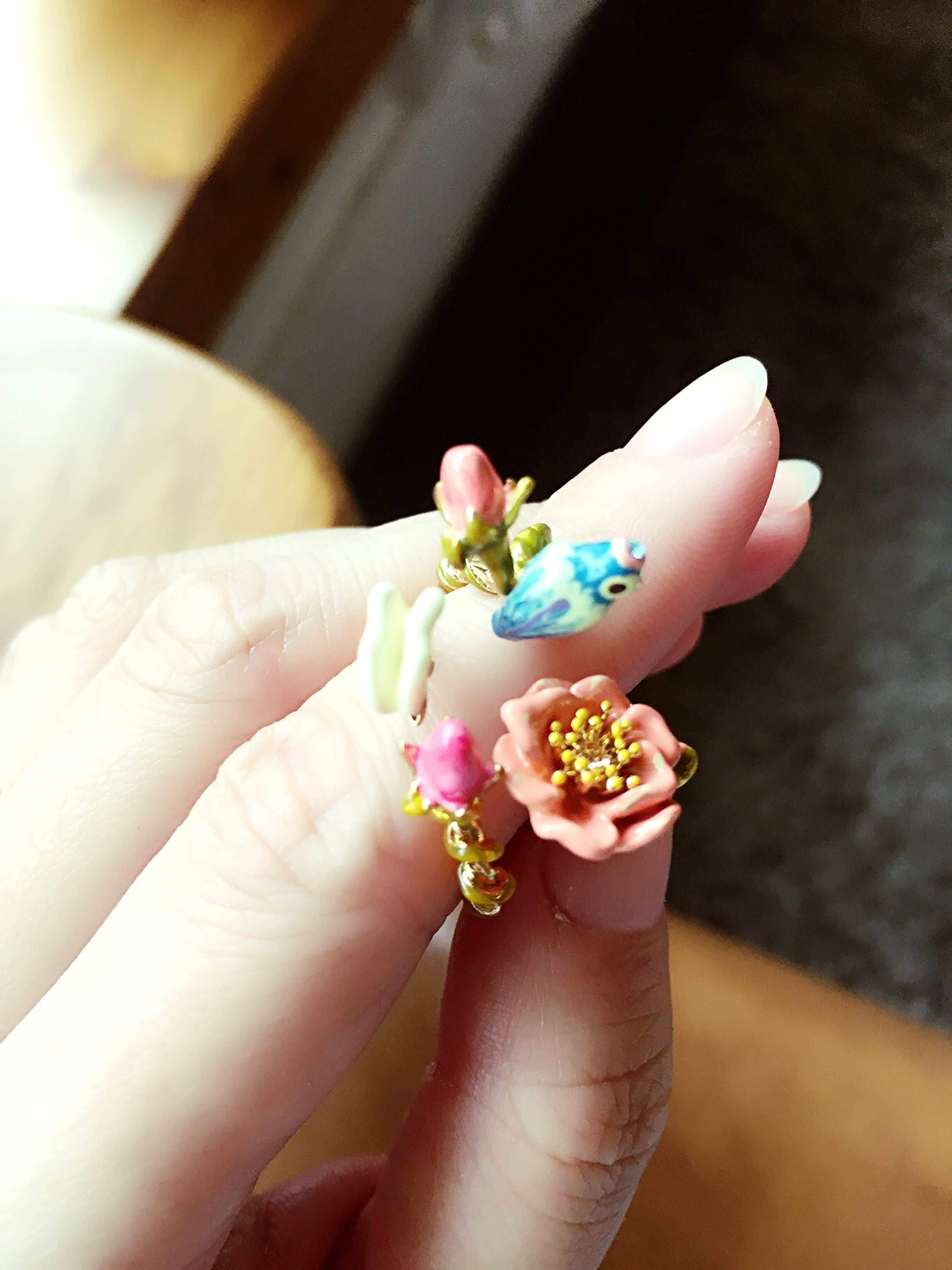 person, flower, holding, part of, human finger, indoors, petal, lifestyles, cropped, personal perspective, freshness, fragility, close-up, flower head, focus on foreground, leisure activity