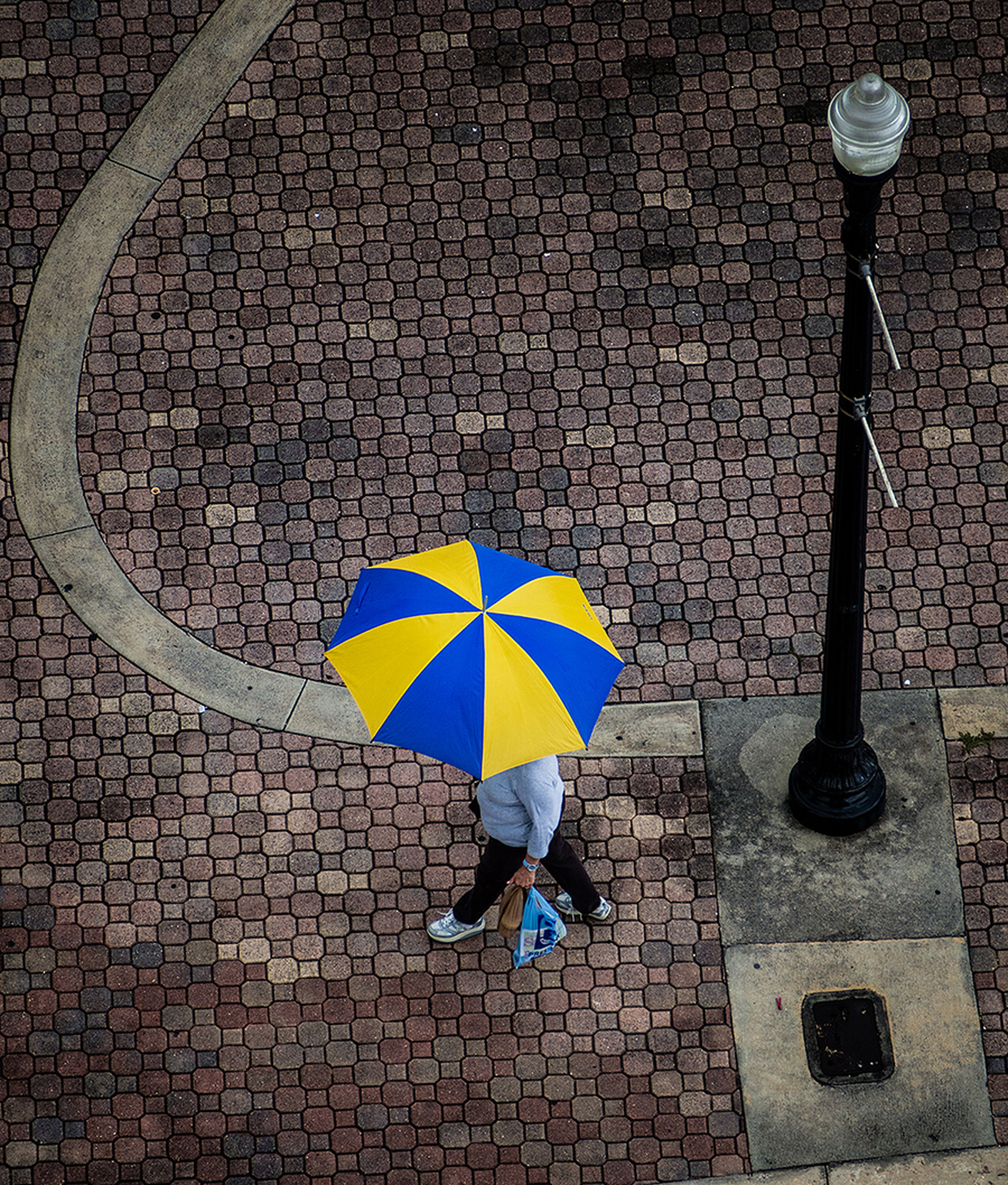 umbrella, cobblestone, art and craft, art, multi colored, creativity, wall - building feature, street, pattern, built structure, tiled floor, high angle view, day, paving stone, sidewalk, brick wall, outdoors, architecture, shadow, wall