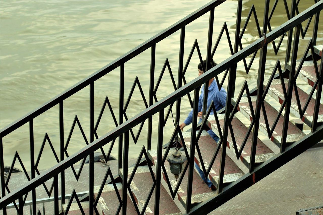 railing, full length, staircase, one person, high angle view, steps and staircases, steps, real people, outdoors, day, men, climbing, hand rail, one man only, adult, adults only, people