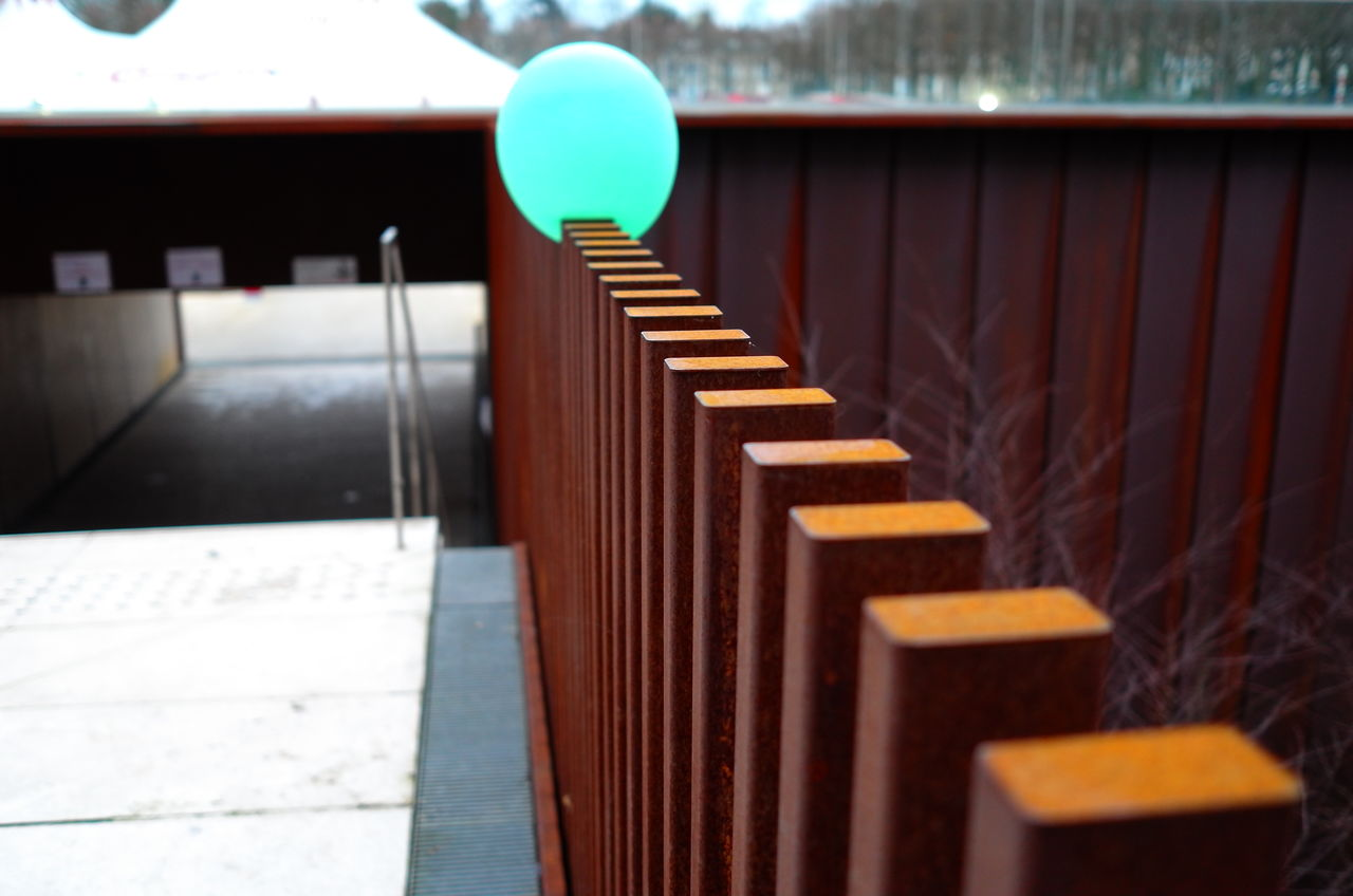 Turquoise balloon trapped on wooden railing during sunny day
