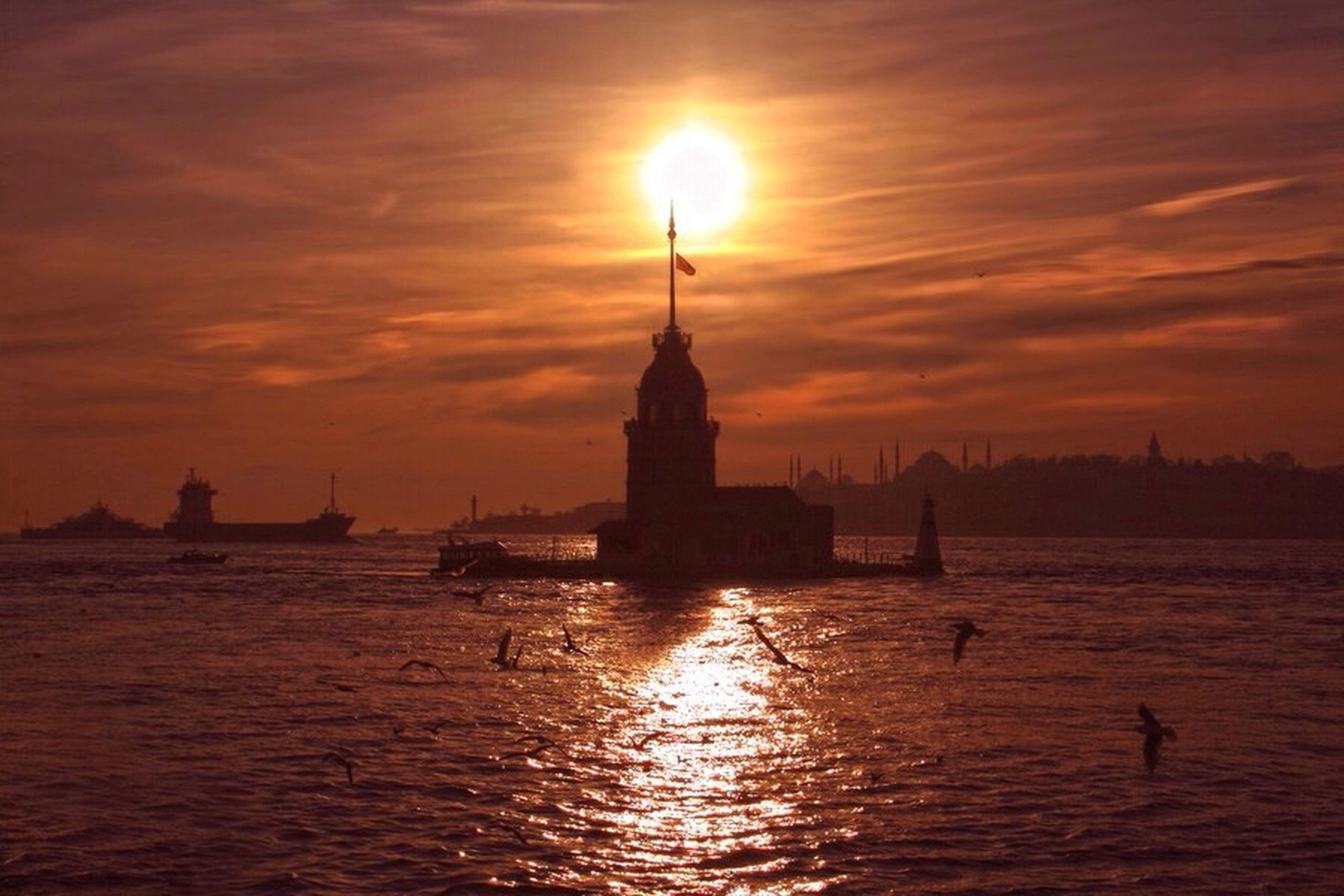 sunset, water, orange color, silhouette, sky, sun, scenics, sea, tranquil scene, tranquility, reflection, beauty in nature, waterfront, idyllic, nature, built structure, cloud - sky, architecture, building exterior, lighthouse