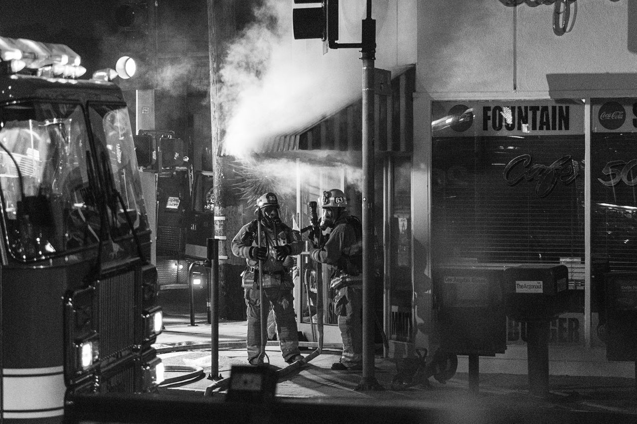Adult Blackandwhite Building Exterior Built Structure Burning Cafe City Fire Firefighter Full Length Lifestyles Men Metal Industry Monochrome Night Outdoors People Protective Workwear Real People Smoke - Physical Structure Two People Welcome To Black