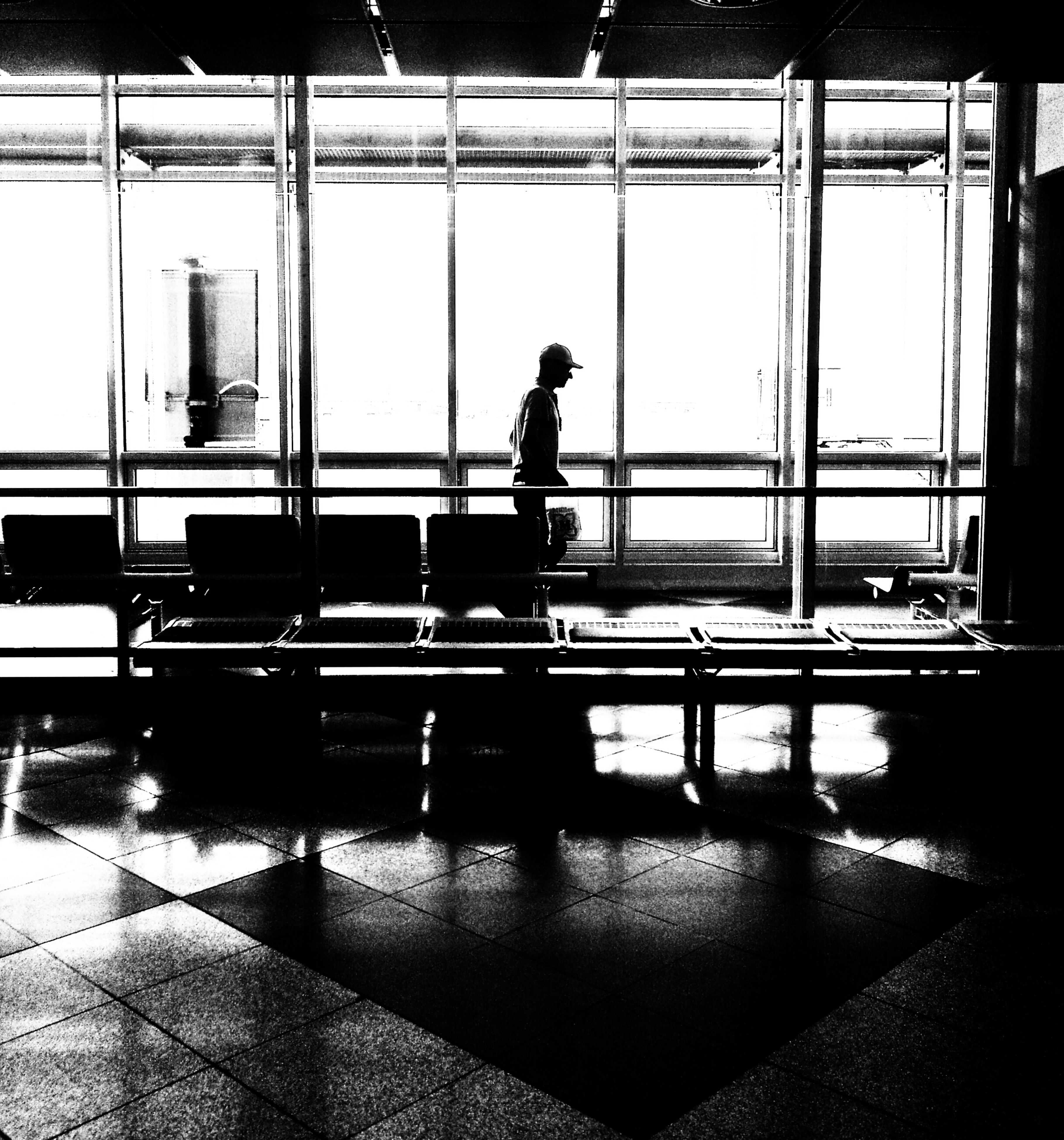 indoors, men, reflection, silhouette, built structure, architecture, window, full length, transportation, lifestyles, glass - material, person, transparent, leisure activity, standing, travel, mode of transport, city life