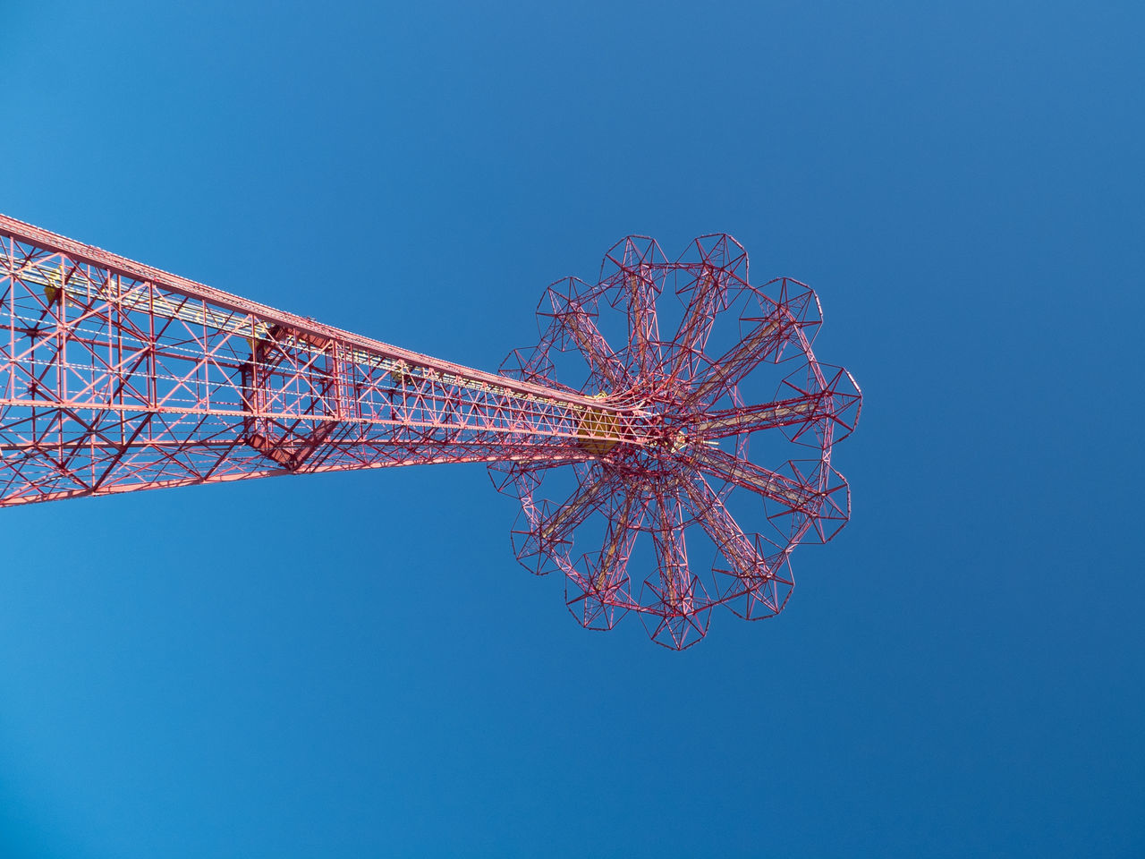 Low Angle View Of Parachute Jump Against Clear Blue Sky