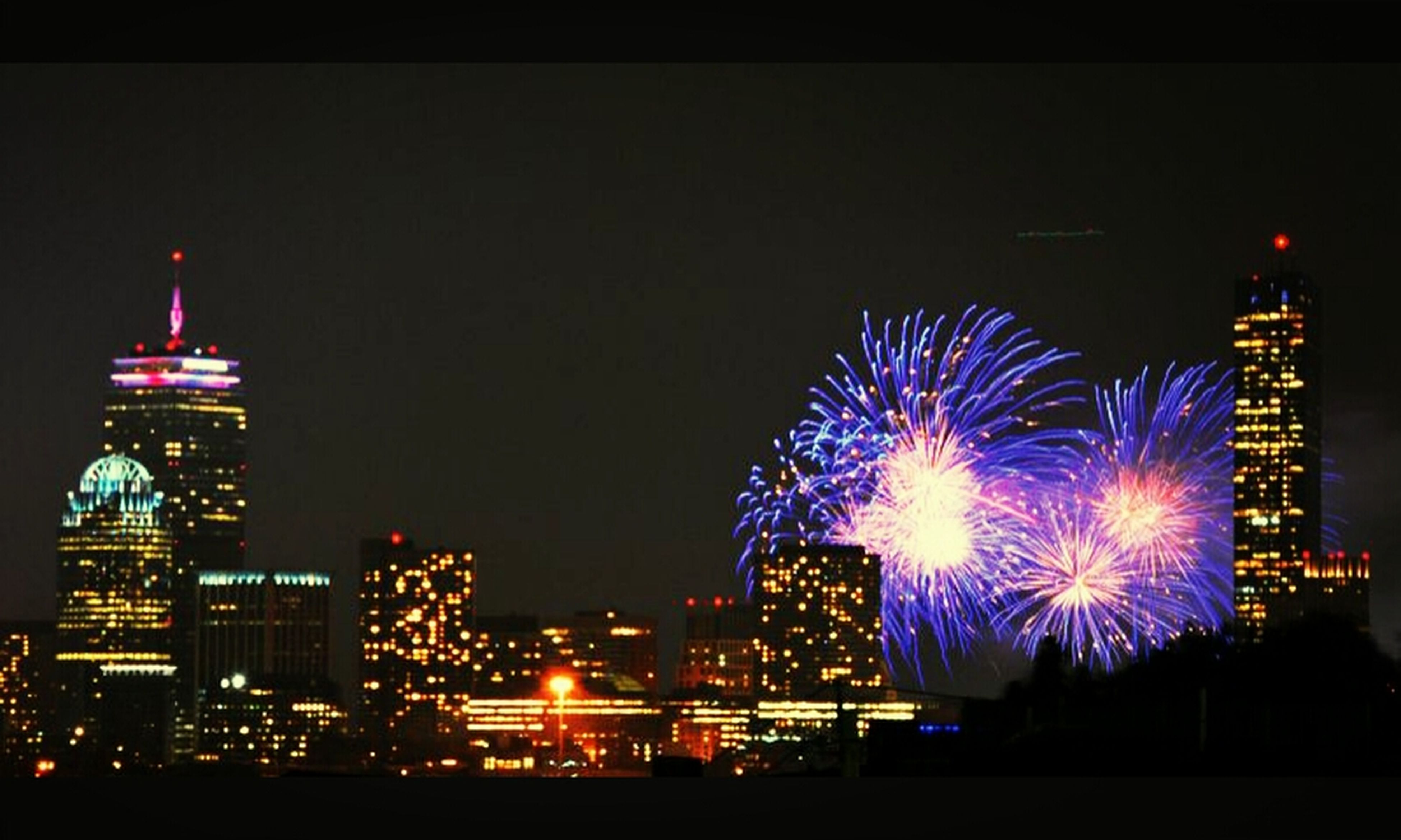 illuminated, night, long exposure, building exterior, city, firework display, built structure, architecture, multi colored, cityscape, glowing, celebration, arts culture and entertainment, sky, exploding, motion, firework - man made object, travel destinations, city life, skyscraper