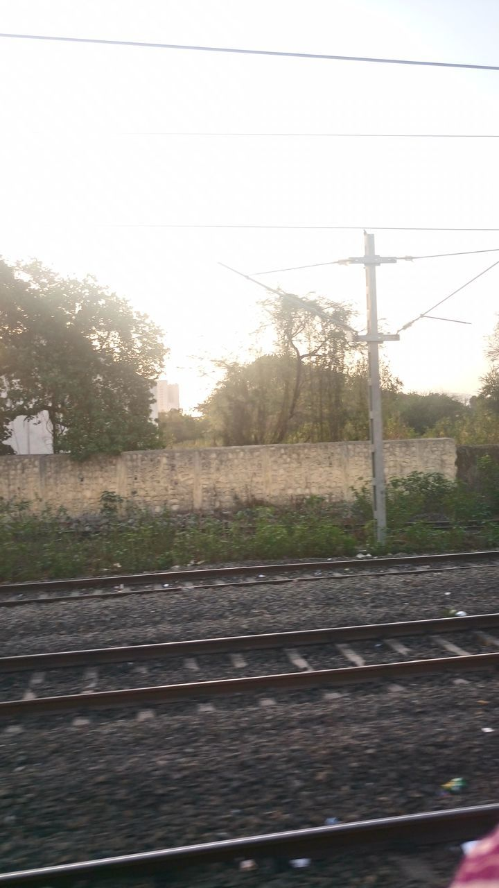 sun, cable, railroad track, tree, no people, rail transportation, day, outdoors, sky, sunlight, transportation, power supply, electricity, electricity pylon, nature, clear sky, sunset, close-up