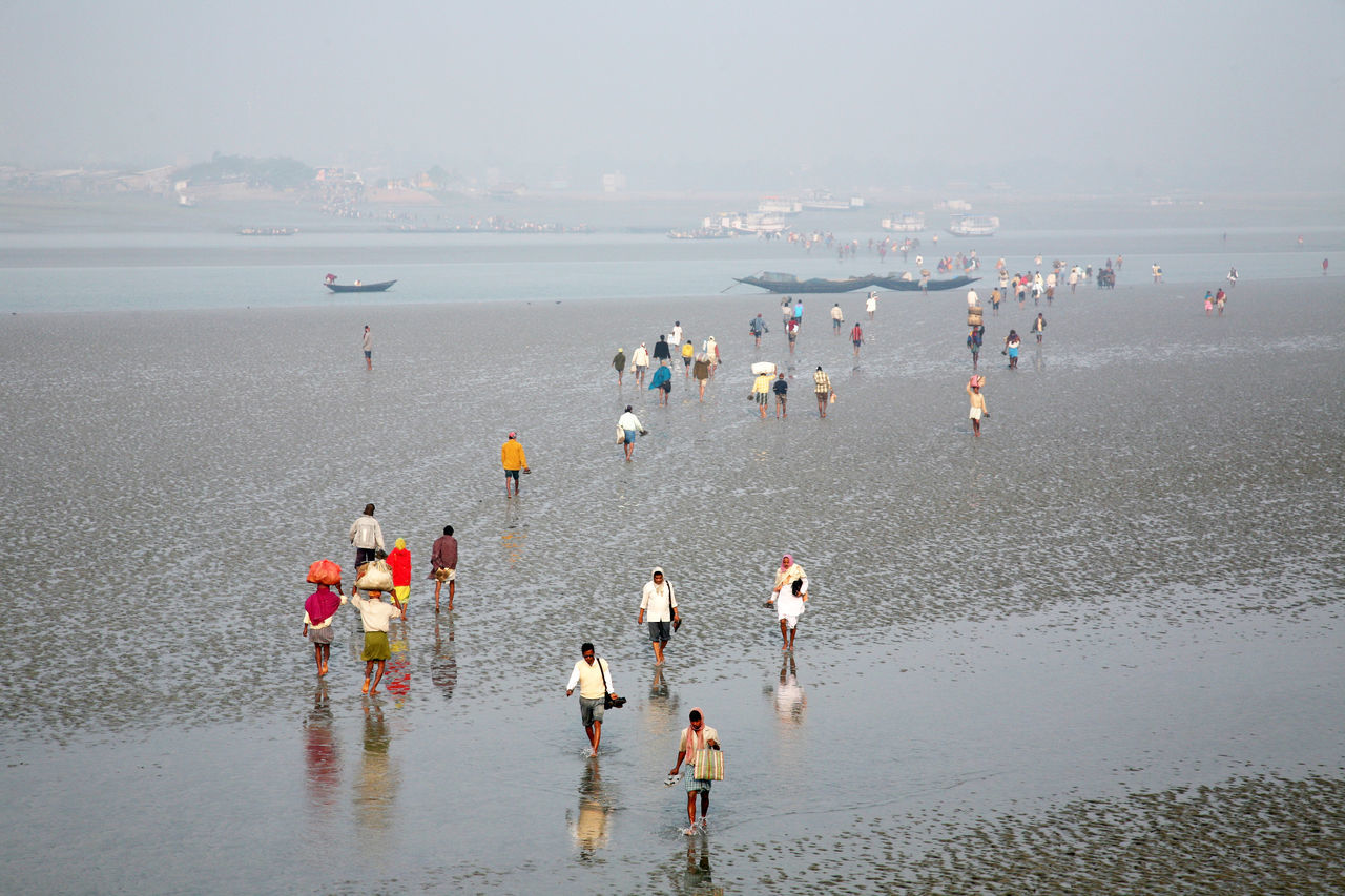 During low tide the water in the river Malta falls so low that people walk to the other shore in Canning Town, India on January 17, 2009. ASIA Canning Coast Ebb India Large Group Of People Low Tide Malta Men Mud River Shore Tide Town Walking Water West Bengal