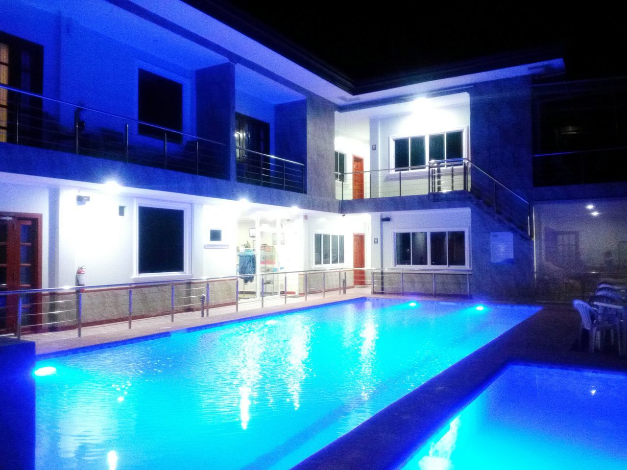 swimming pool, water, illuminated, night, poolside, architecture, building exterior, built structure, luxury, reflection, tourist resort, blue, luxury hotel, no people, outdoors, sky
