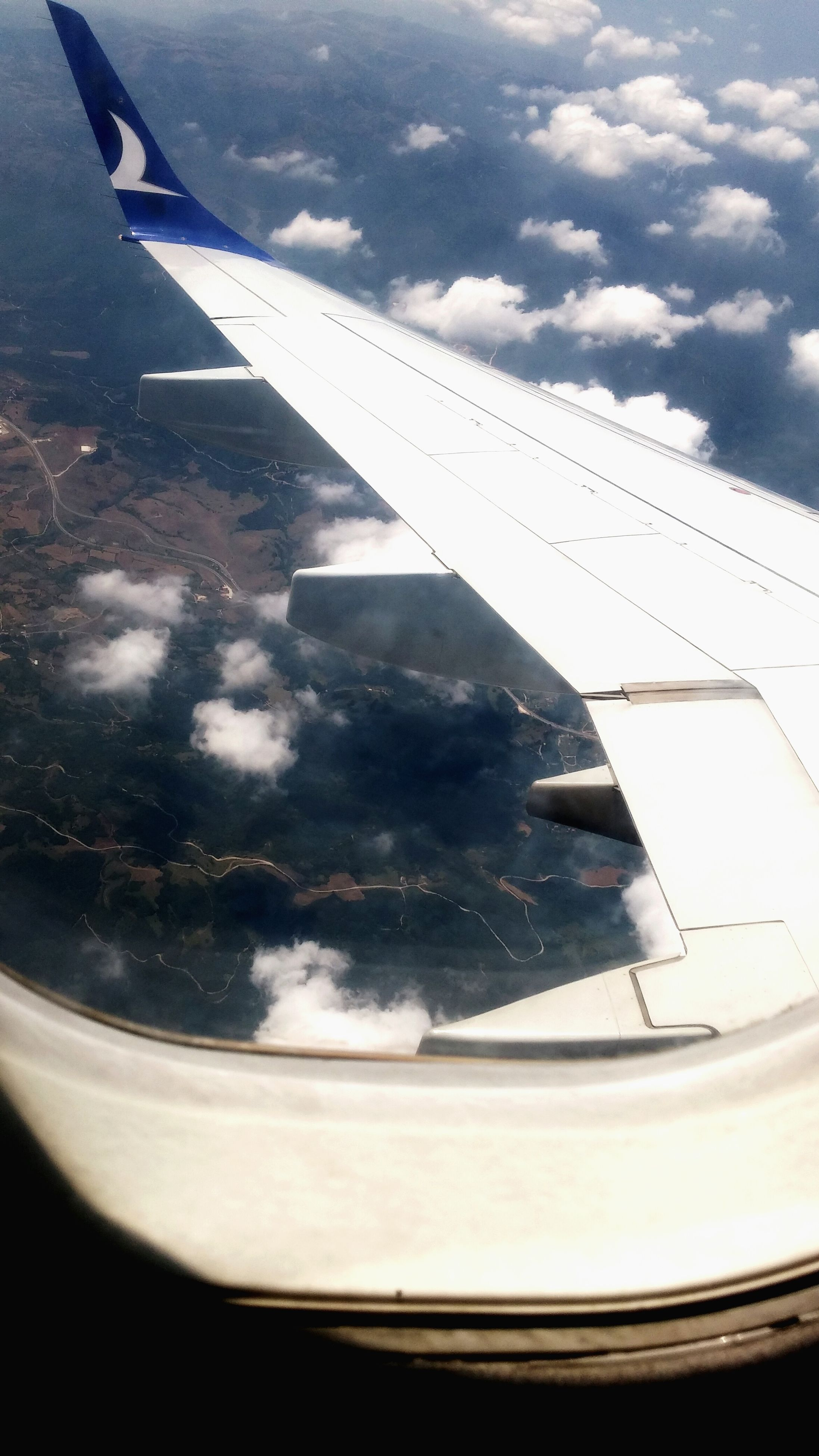 airplane, aircraft wing, transportation, air vehicle, flying, mode of transport, part of, cropped, aerial view, mid-air, travel, on the move, sky, airplane wing, vehicle part, journey, cloud - sky, public transportation, nature, aeroplane