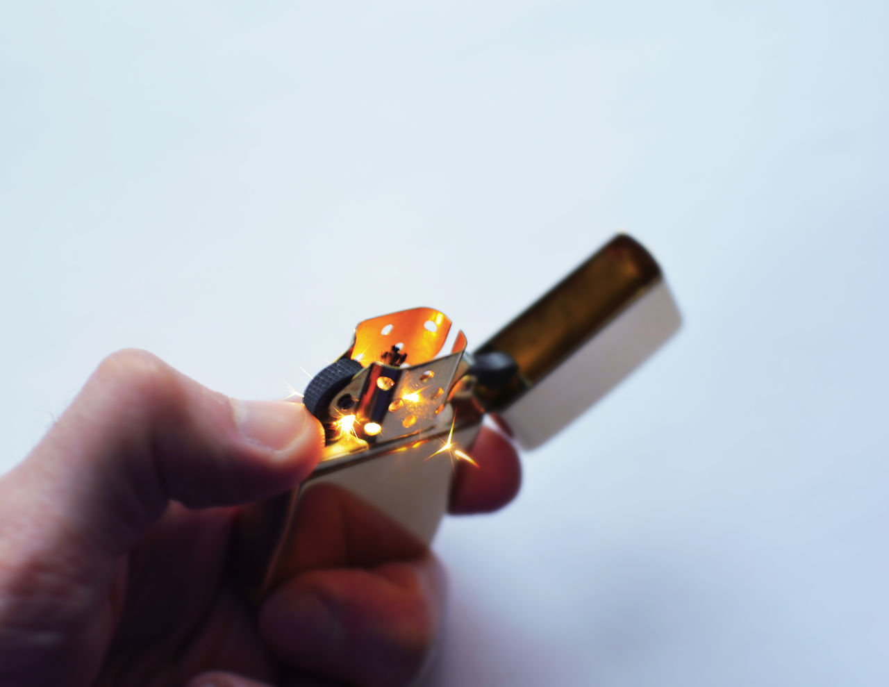 A classic Zippo lighter sparking to life. American Burn Classic Close Up EyeEmNewHere Glow Holding Holding Zippo Human Hand Iconic Iconic Design Indoors  Lighter Lighter Flame Lit Luxury Macro Orange Smoker Spark Studio Shot Traditional Lighter White Background Zippo Zippo Lighter