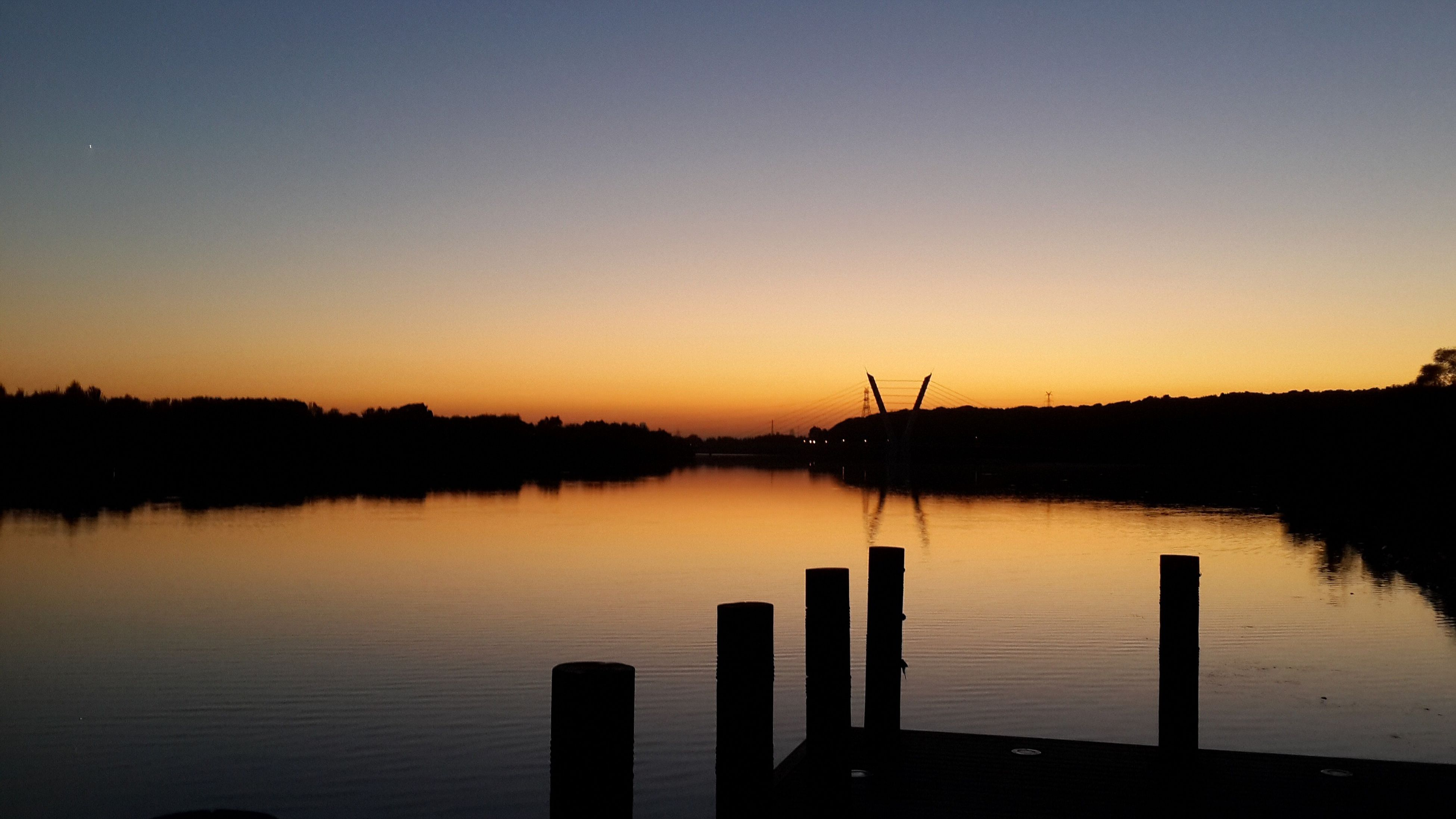 water, sunset, reflection, lake, tranquil scene, silhouette, tranquility, clear sky, copy space, scenics, beauty in nature, nature, waterfront, idyllic, dusk, calm, wooden post, river, outdoors, no people