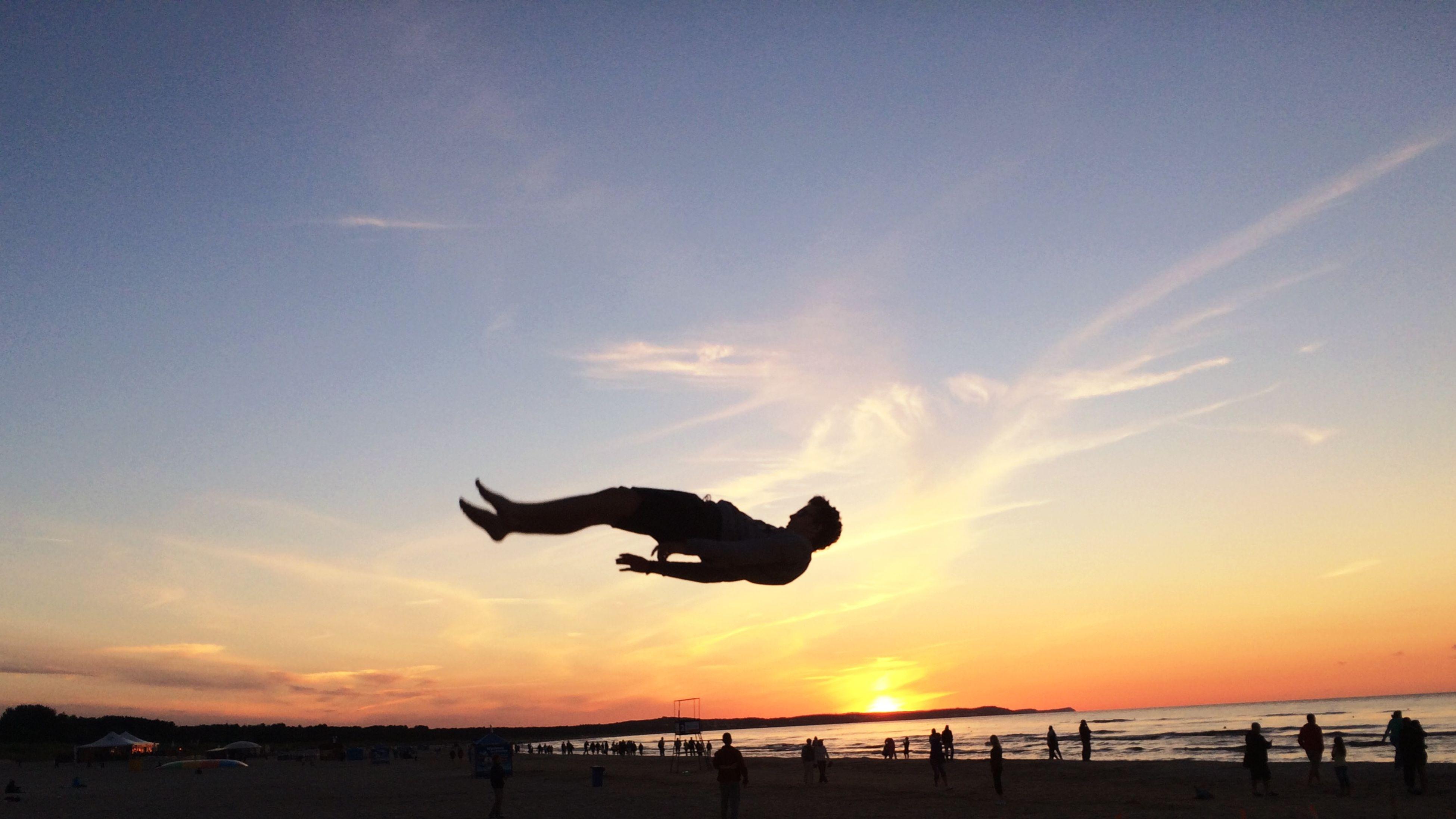 silhouette, sunset, sky, leisure activity, sea, beach, lifestyles, horizon over water, sun, men, enjoyment, scenics, beauty in nature, nature, mid-air, sunlight, full length, cloud - sky