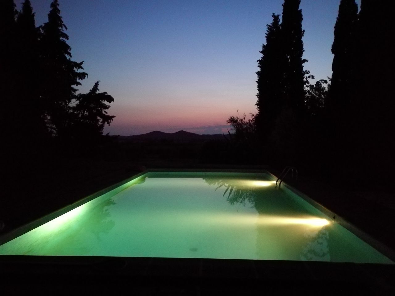 swimming pool, water, tree, no people, night, sunset, silhouette, illuminated, tranquility, nature, growth, outdoors, sky, beauty in nature