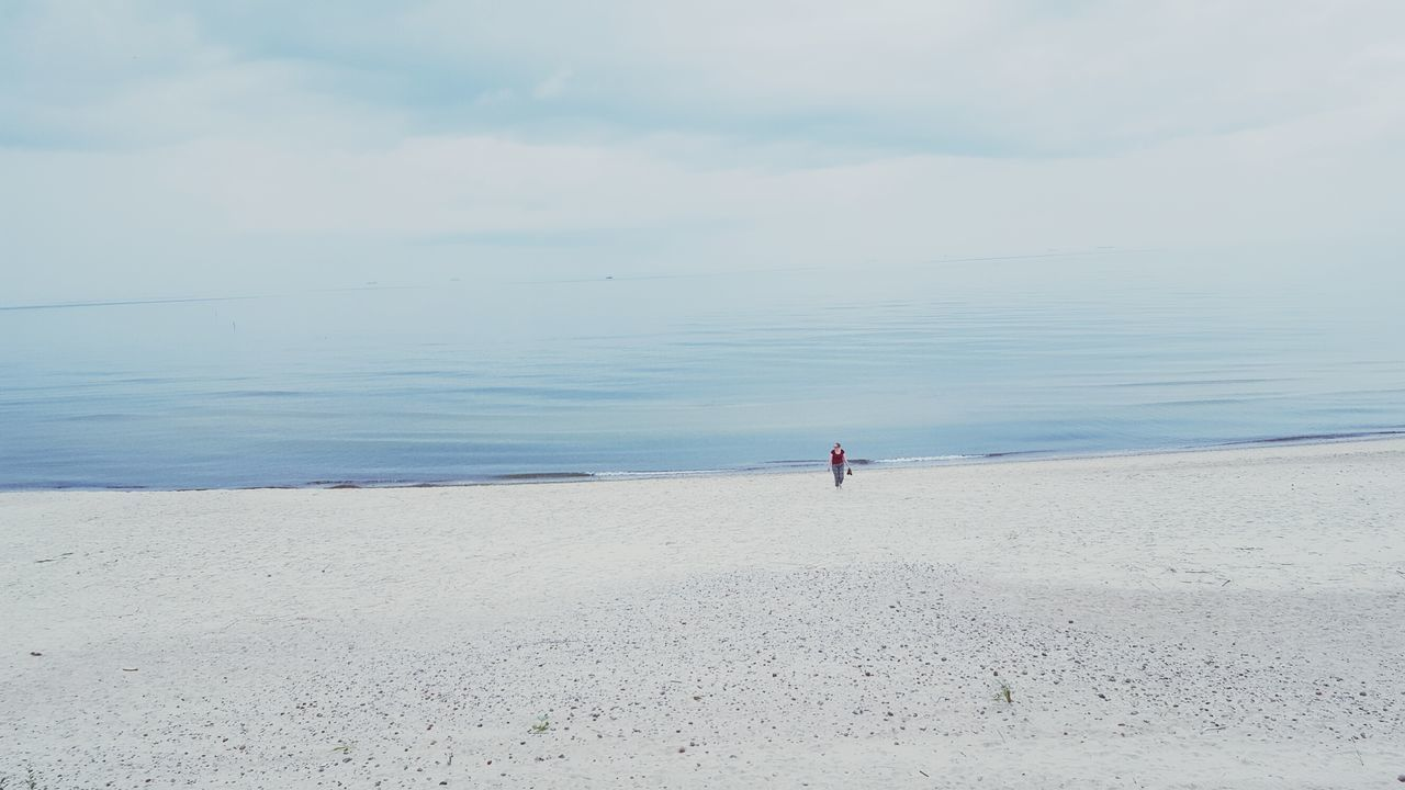 Distant Image Of Woman Walking On Beach