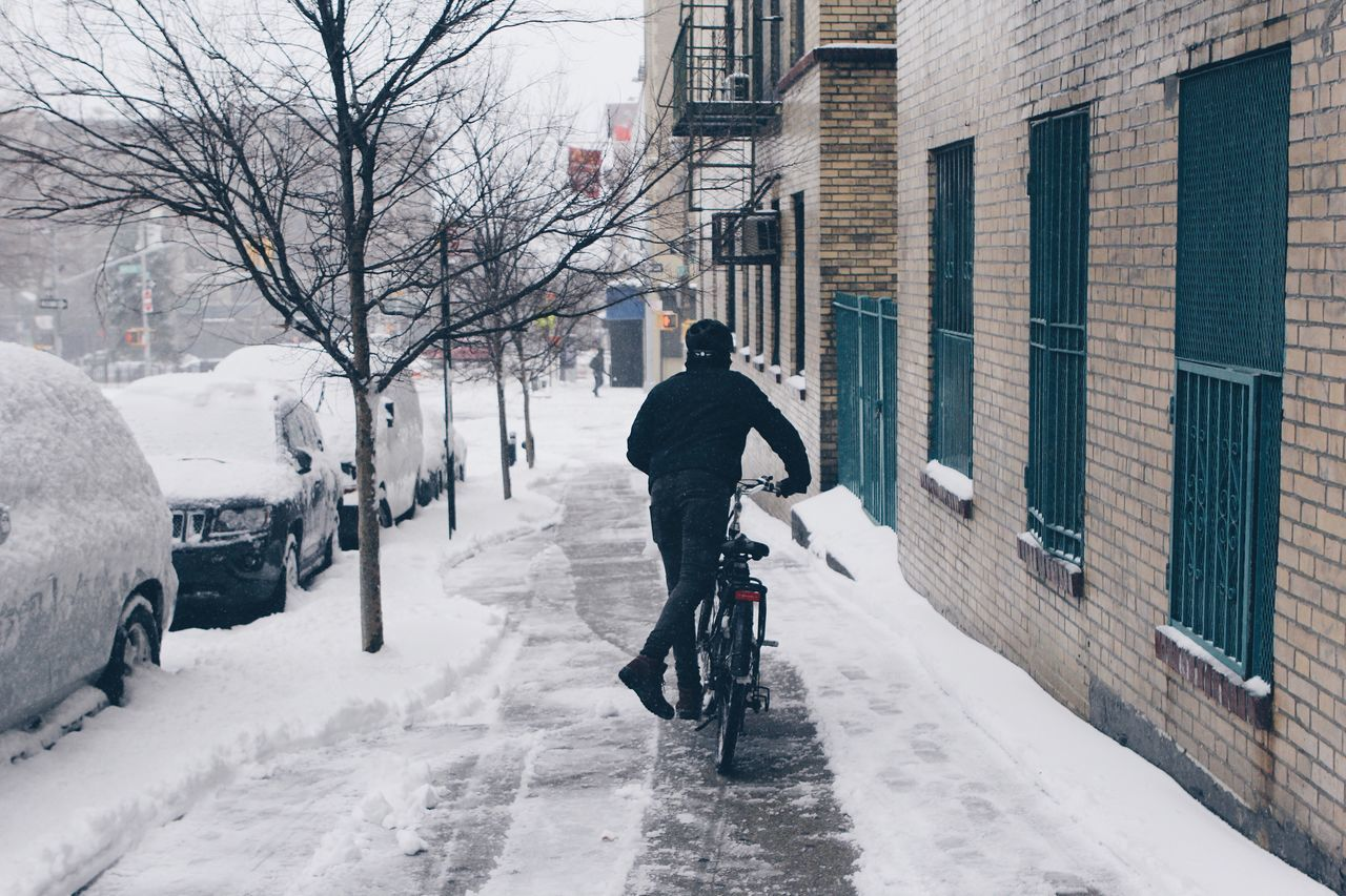 City Cold Temperature Snow Winter Bicycle One Man Only One Person City Street Building Exterior Only Men Adults Only Transportation City Life Outdoors Warm Clothing Stationary Rear View Full Length Architecture Cycling