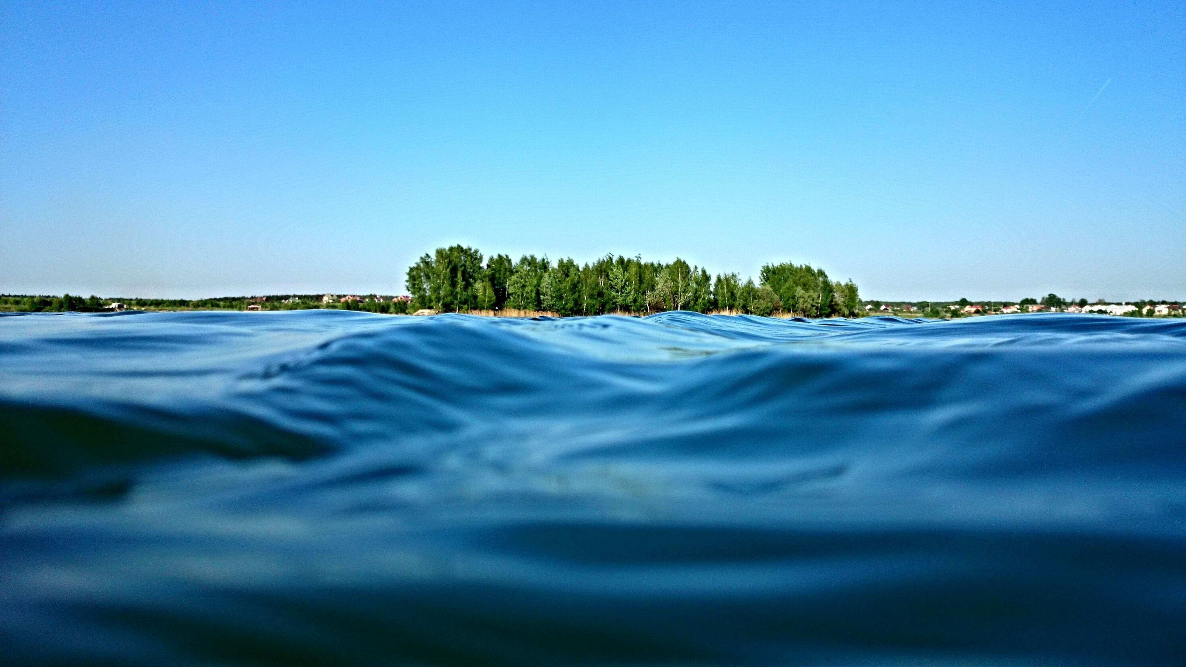 clear sky, water, blue, copy space, waterfront, rippled, tranquil scene, tranquility, sea, scenics, beauty in nature, nature, tree, idyllic, outdoors, day, river, no people, lake, calm