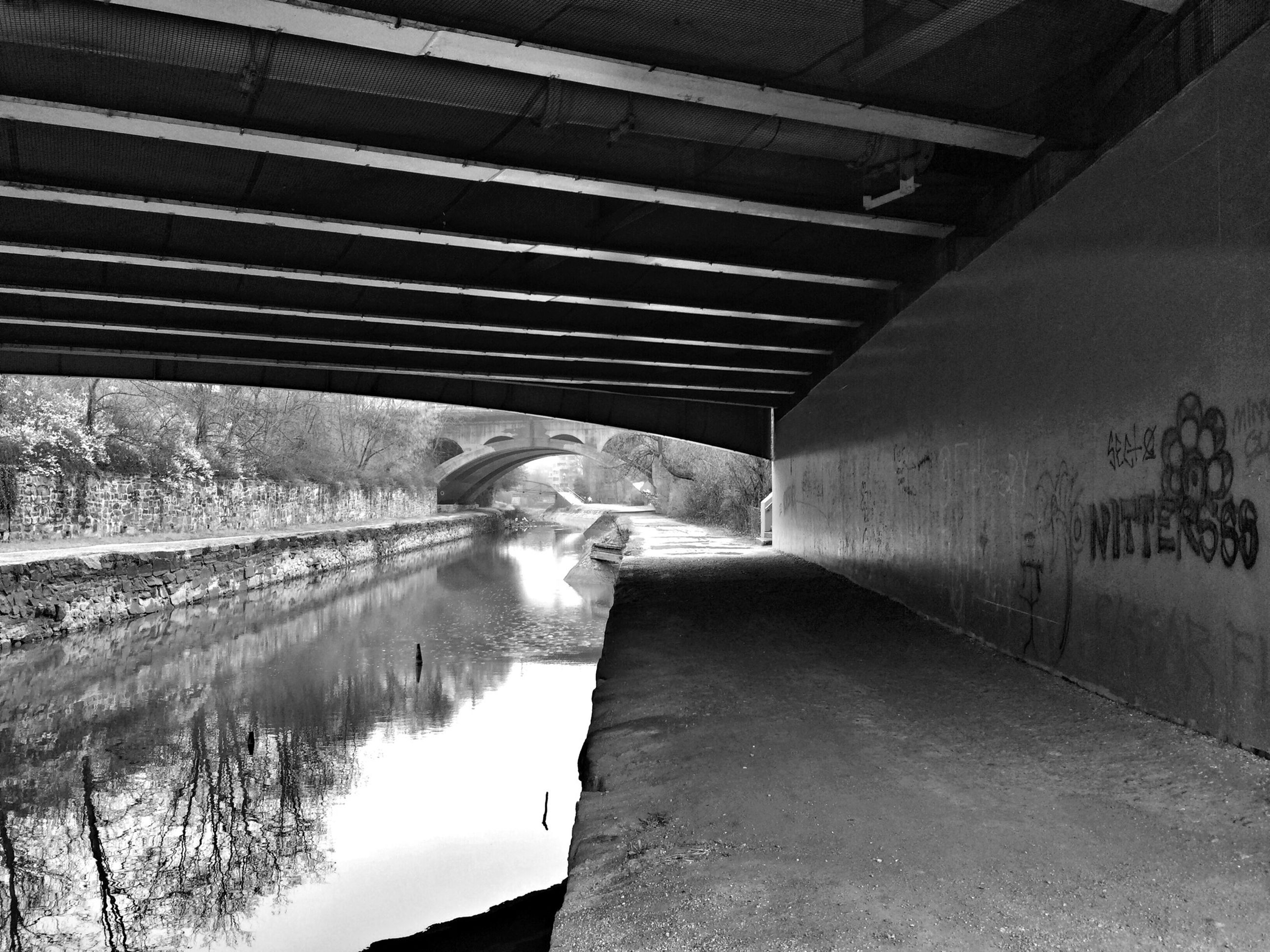 architecture, the way forward, built structure, water, reflection, bridge - man made structure, one person, diminishing perspective, connection, transportation, building exterior, tunnel, puddle, vanishing point, full length, day, railing, canal, road, walking