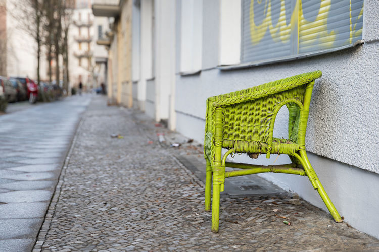 Berlin's abandoned chairs. Last step before disposal of old, lime green wicker chair on cobblestone footpath. Abandoned Aging Process Architecture Bad Condition Building Exterior Built Structure Chair City Cityscape Cobblestone Damaged Deterioration Empty Footpath Green Color No People Obsolete Old Outdoors Retirement Seat Single Object The Past Weathered Wicker
