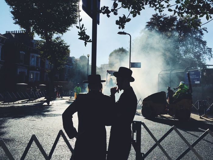 Two Hasidic Jewish men having a conversation while watching the local roadworks. Chat City City Life Construction Work Conversation Corner Hasidic Jewish Jews Listening London Mid Conversation Outdoors Roadworks Roller Sky Street Sun Sunbeam Sunlight Sunny Talk Thought Tree