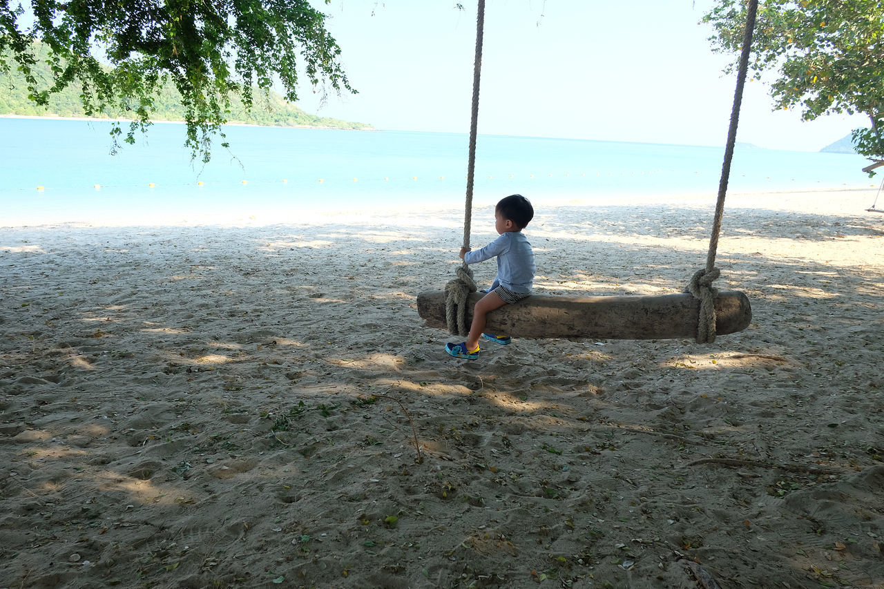 Beach Beauty In Nature Childhood Day Full Length Nature One Person Outdoors People Real People Sand Sea Sitting Sky Swing Tree Water