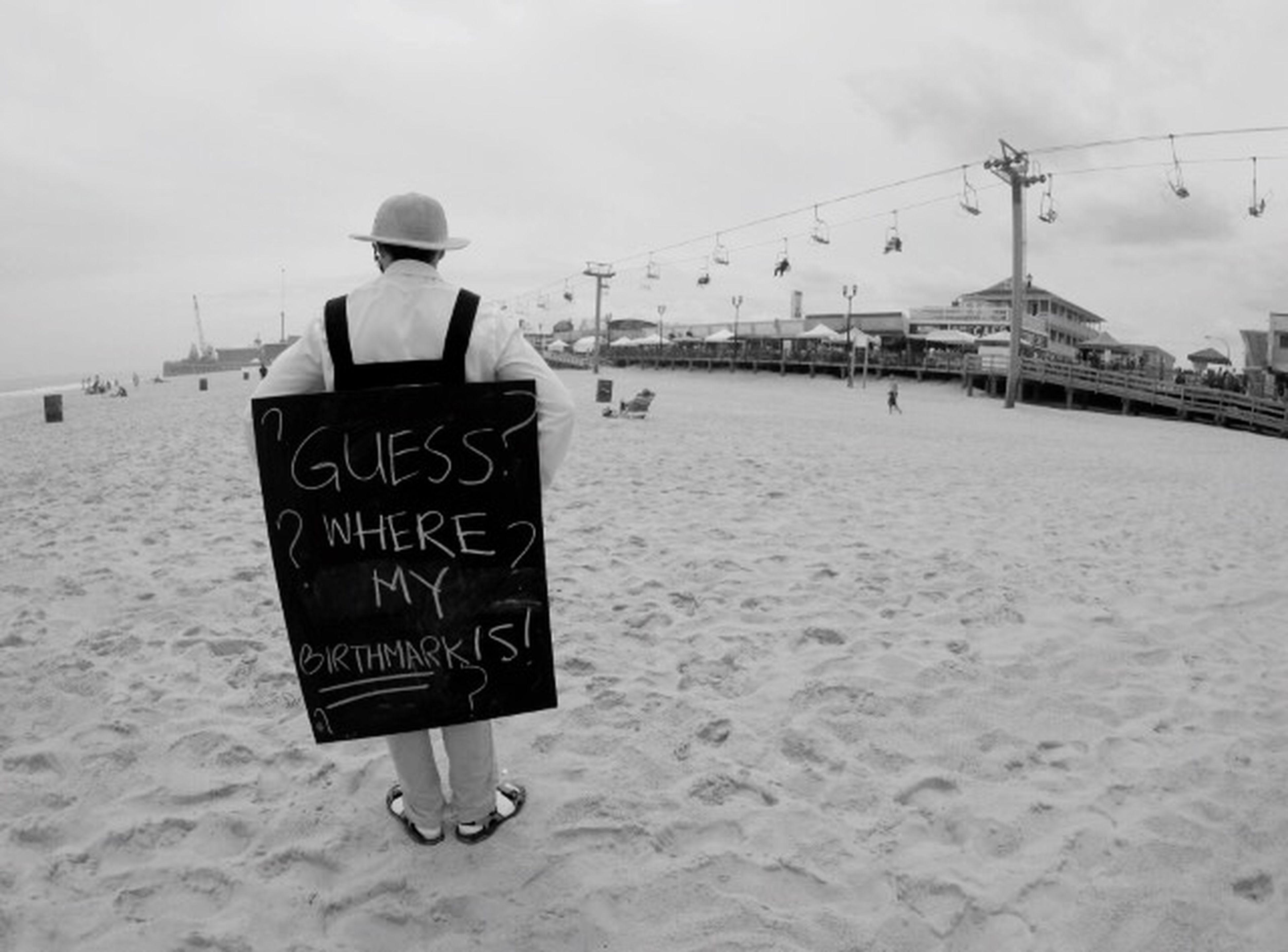 sky, text, beach, sand, lifestyles, incidental people, western script, built structure, sea, leisure activity, communication, men, full length, outdoors, street, architecture, walking, rear view