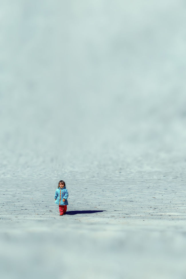 a girl walks across the sand Beauty In Nature Childhood Day Leisure Activity Lifestyles Nature One Person Outdoors People Real People Scenics Sea Sitting Water Young Adult Young Women Girl In A Blue Raincoat Blue Raincoat Red Pants Wite Sands Wite Sand Miniature Effect Miniature Effect Photography Lost In The Landscape Fashion Stories