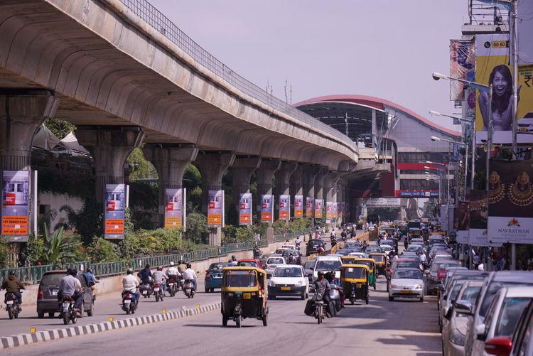 Downtown Bangalore showing M.G. Road, the Metro rail, Autorickshaw, and Traffic.