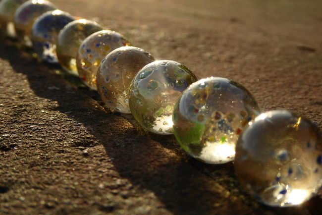 Artistic Photo Ball Bubble Circle Close-up Concrete Wall Diagonal Extreme Close-up Focus On Foreground Gaming Glasball Glass - Material Lines And Shapes Man Made Object Marble No People Raw Reflections Selective Focus Shiny Sparks Sunlight Taw Tranquility Urbanphotography