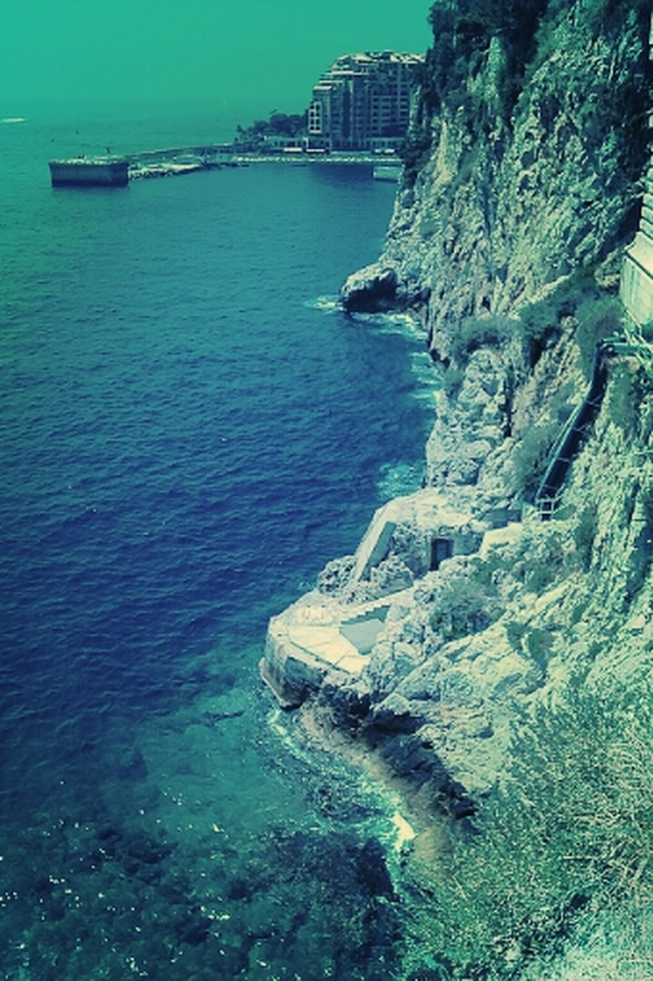 water, sea, waterfront, blue, built structure, nautical vessel, architecture, rock - object, nature, rippled, building exterior, sunlight, transportation, day, turquoise colored, boat, high angle view, outdoors, tranquility, no people